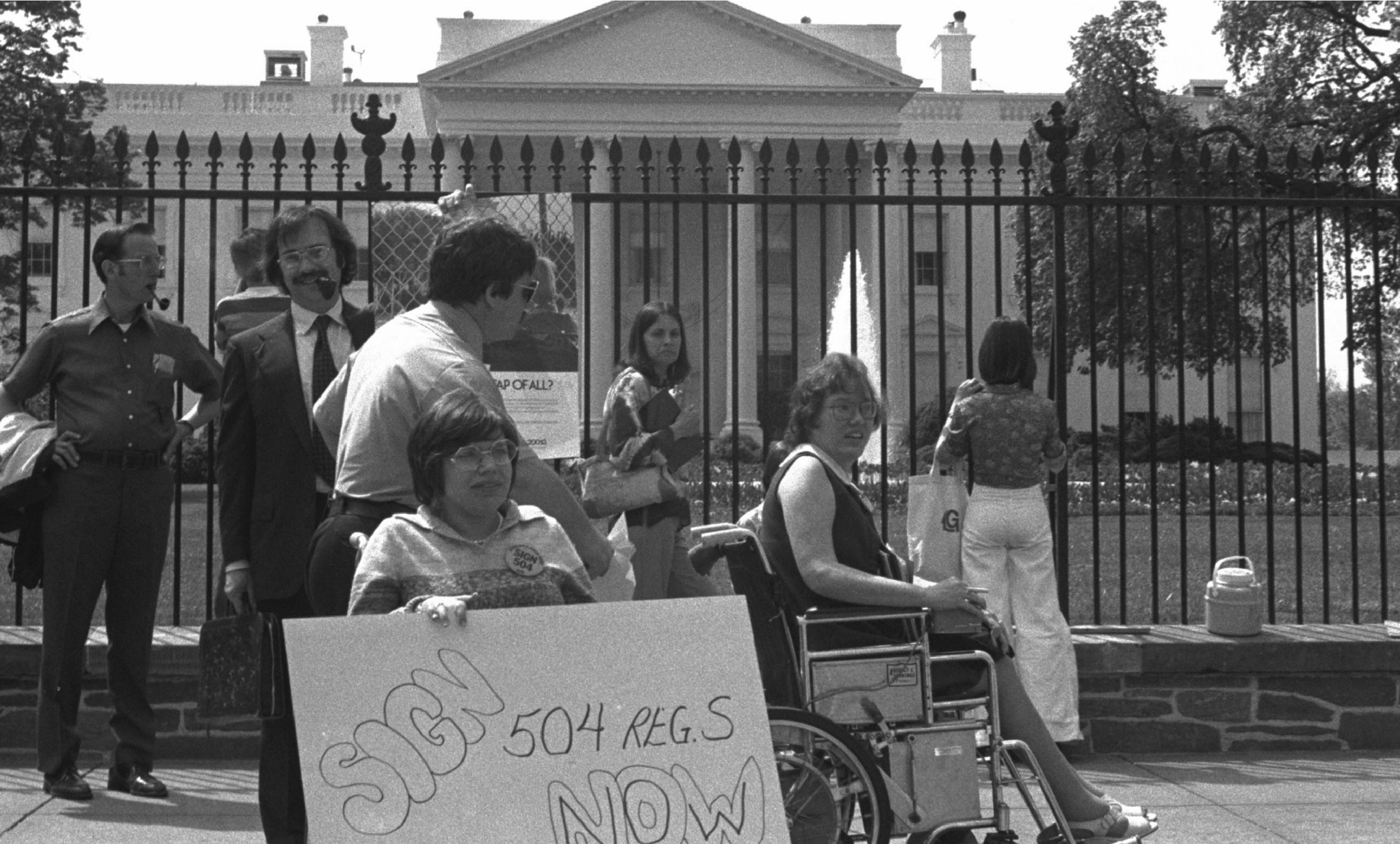 "Heumann is pictured in her wheelchair in front of the White House, holding a sign that reads ""Sign 504 Now."""