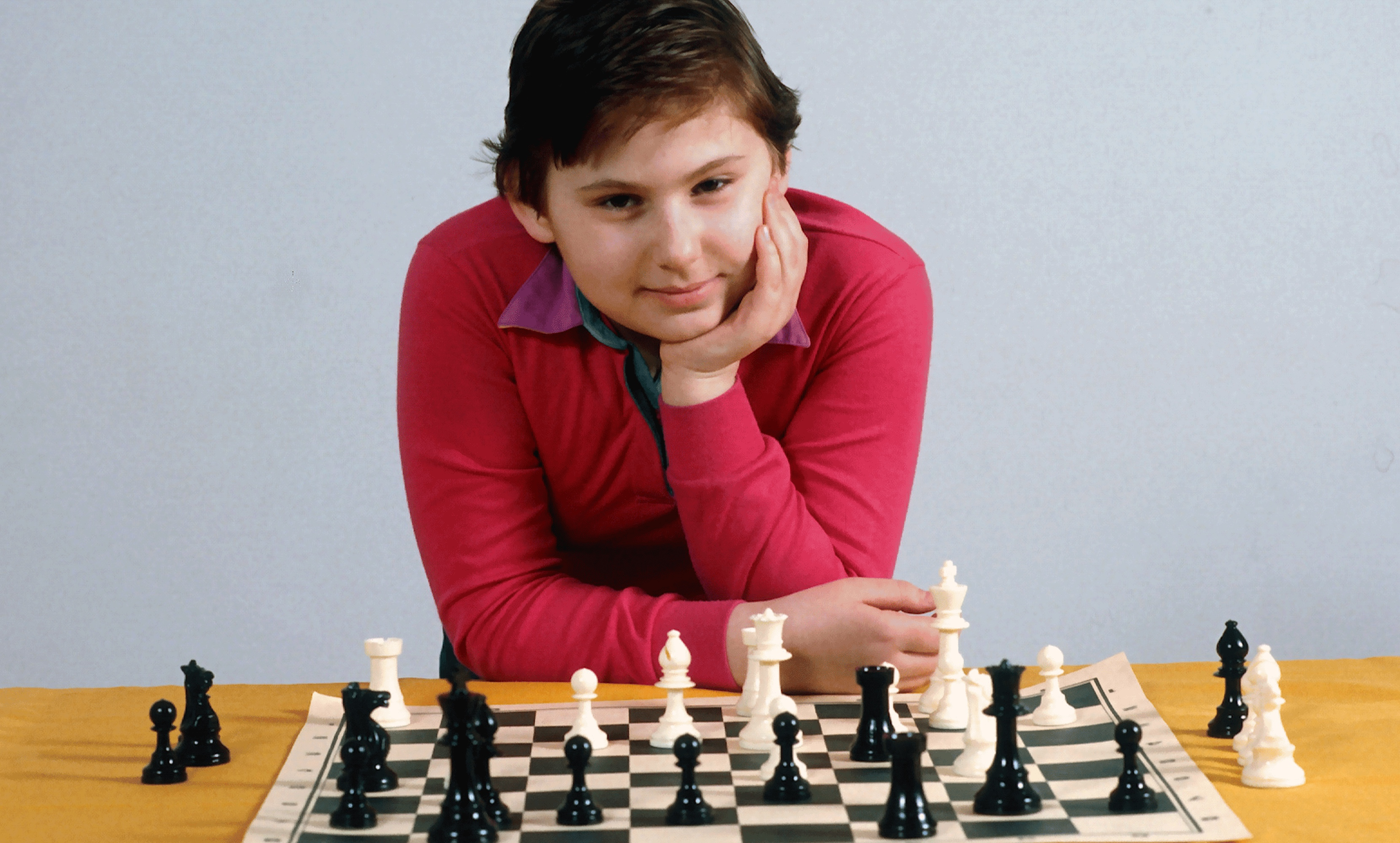 Polgár at age 9. Sporting a bright red shirt and close-cropped hair, she leans over a paper chess board, cupping her face in her hand.