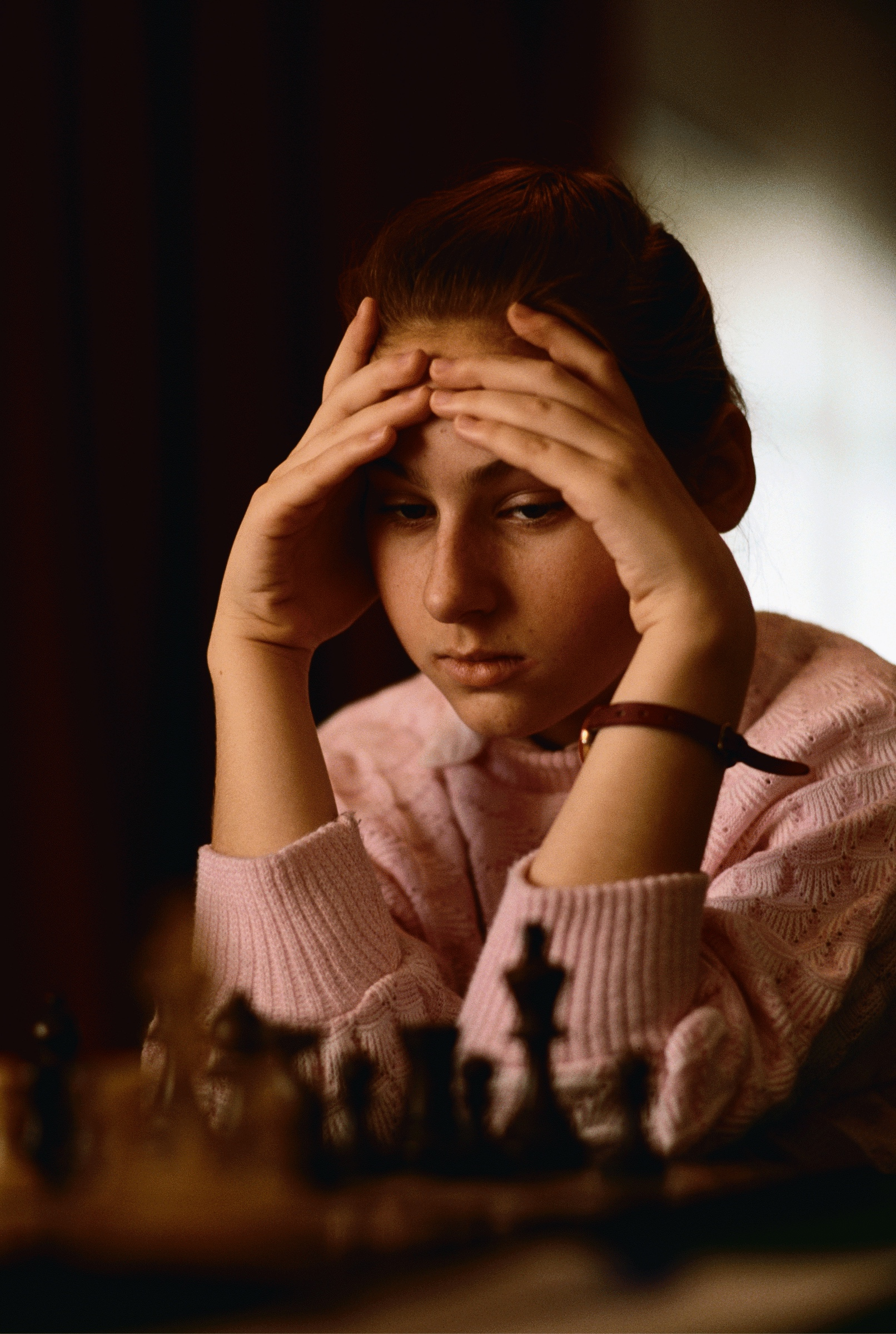 Polgár at age 12. Looking almost like a ballerina in a pink sweater, her hair pulled back, she stares pensively at a chess board.