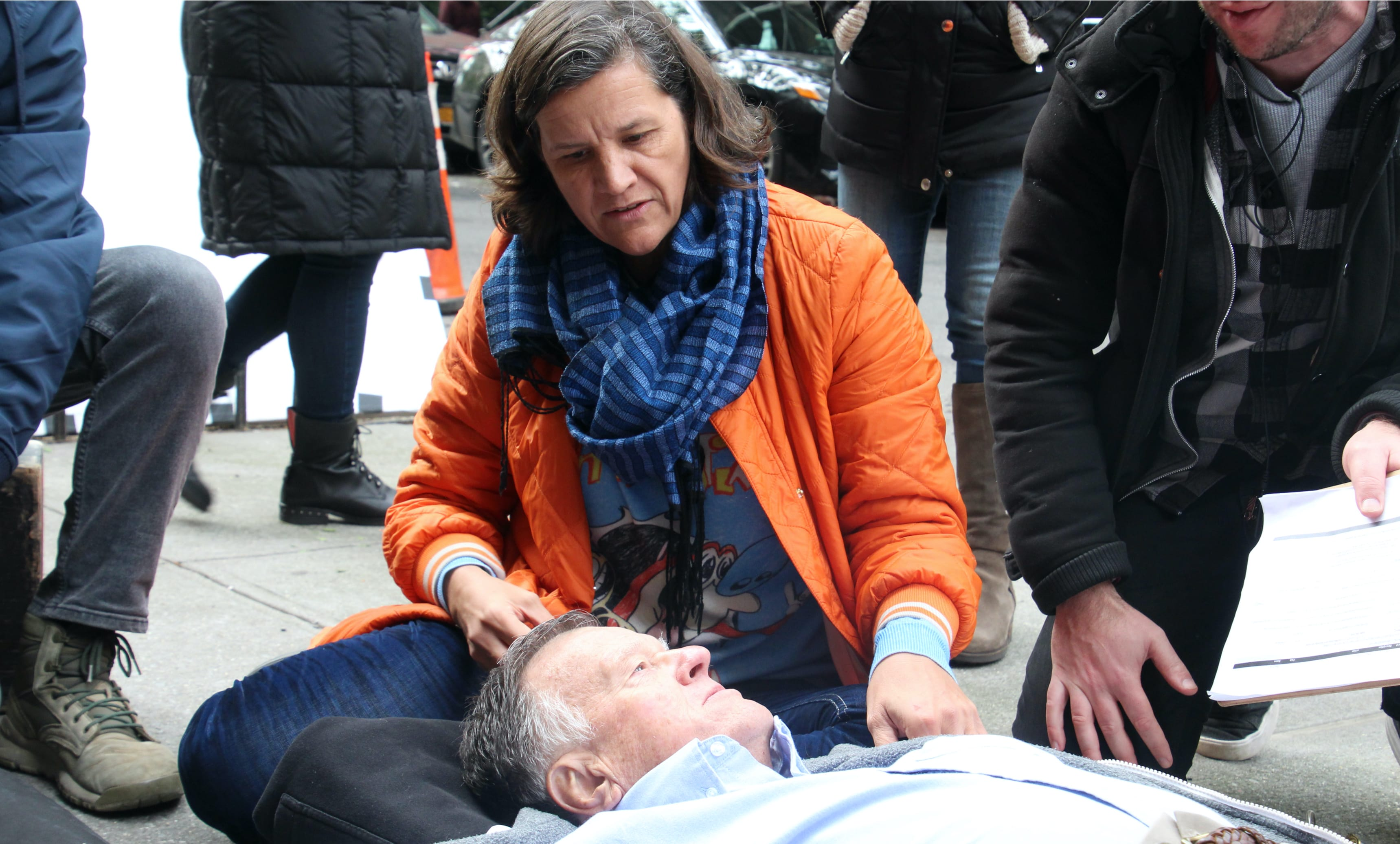 Kirsten Johnson directs her father in one of the deaths the film imagines for him. He lies on the sidewalk with his daughter and some of the crew flocking above him.