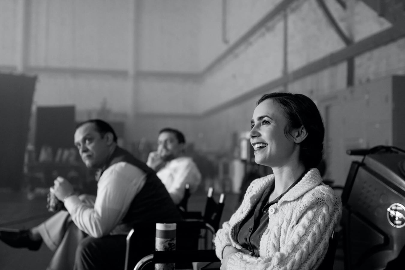 Lily Collins enjoys a moment on the set of Mank. Who's that way in the back? It must be Orson Welles himself!