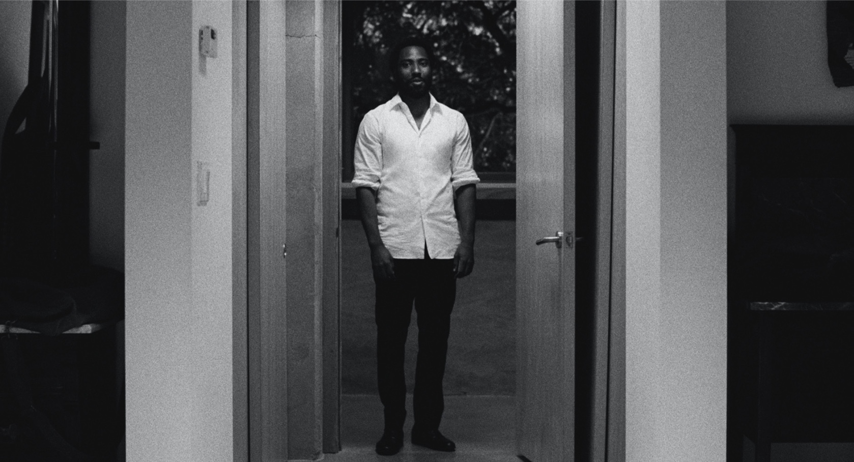 Malcolm framed in a doorway, wearing a white shirt with the sleeves rolled up.