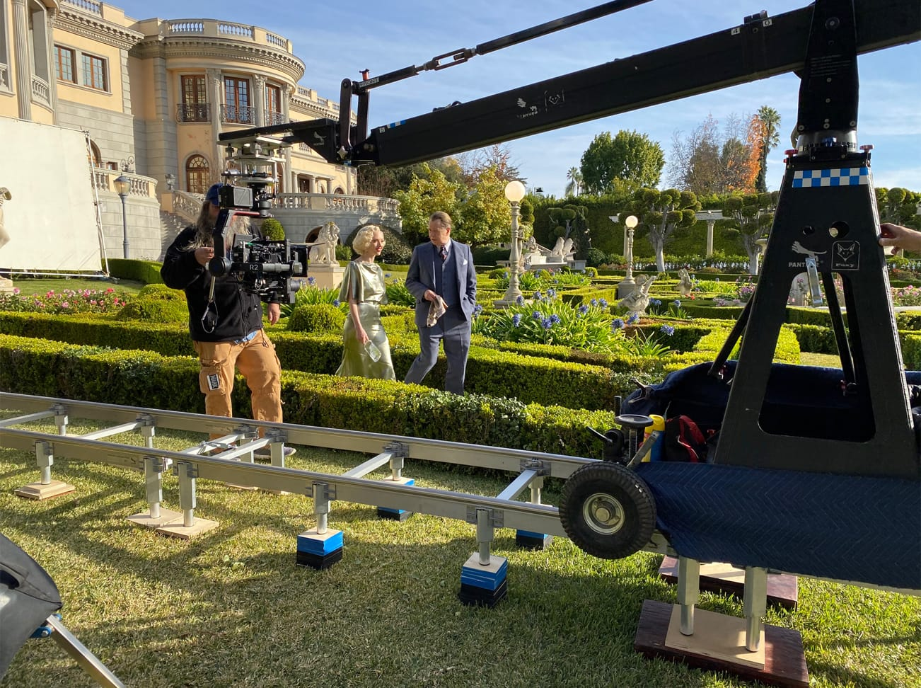 Seyfried and Oldman stroll through the bright green manicured garden that stands in for the Hearst Castle grounds.