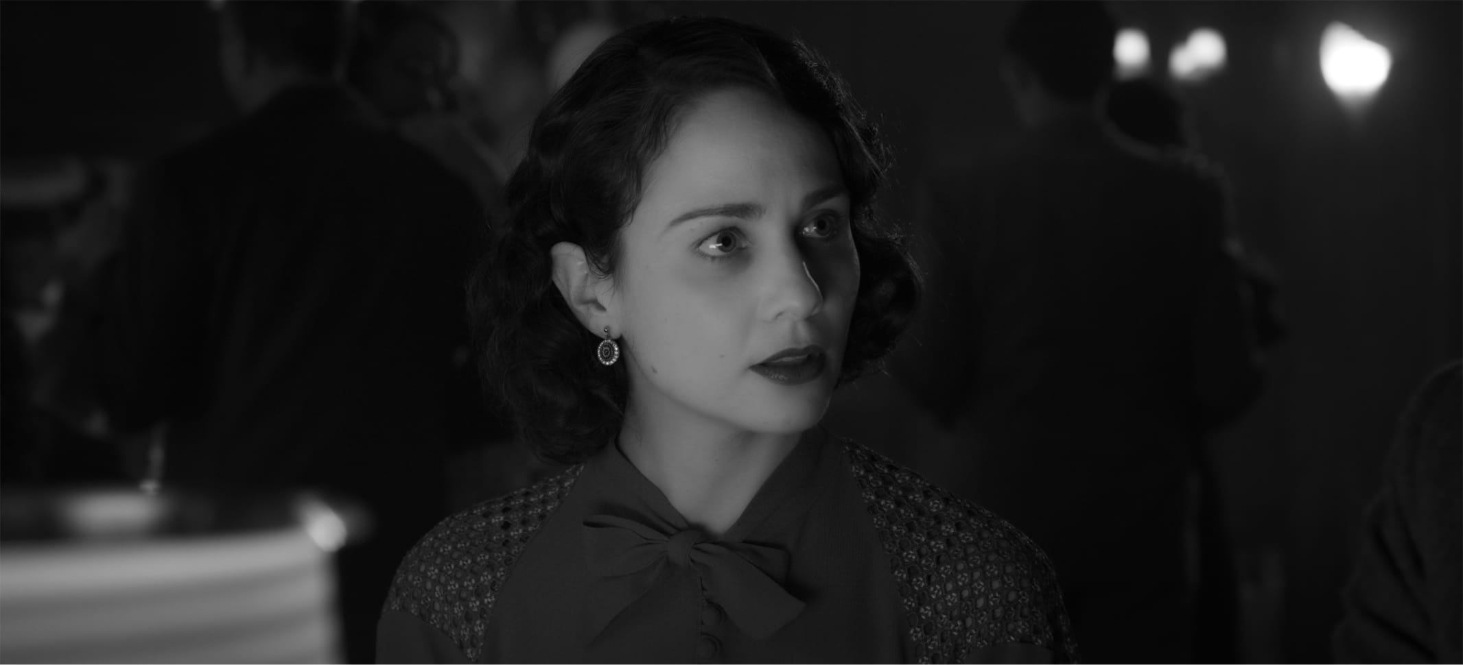 In a shot from the film, we see how the scene above translates to a black-and-white experience. Middleton's dark hair, red dress, and red lipstick appear in rich shades of gray and black.