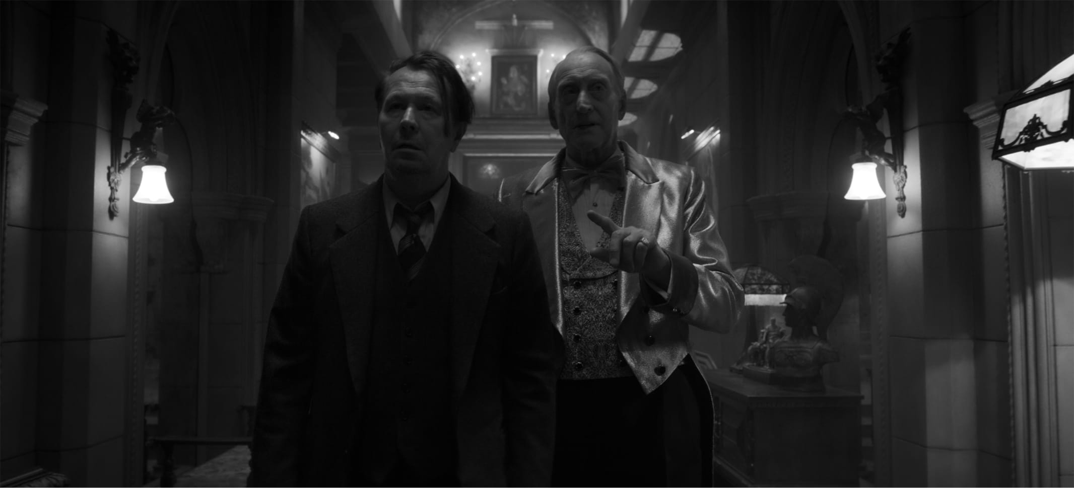 Mank and Hearst, in that bronze get-up, wander the halls of a dusky Hearst Castle in a black-and-white still from the film. The light catches Hearst's jacket.