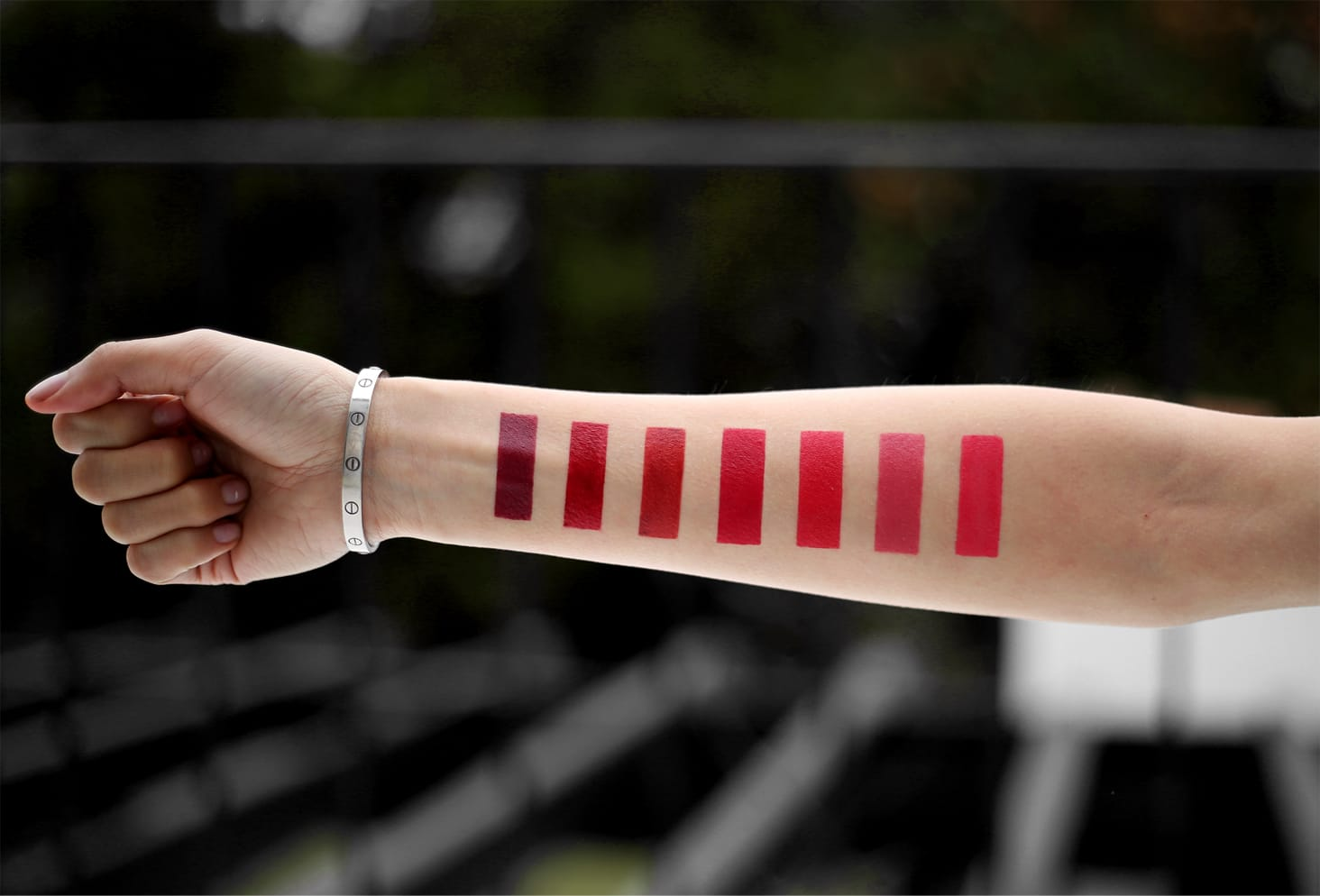 A makeup artist holds out her arm, on which perfectly rectangular lipstick swatches have been drawn.