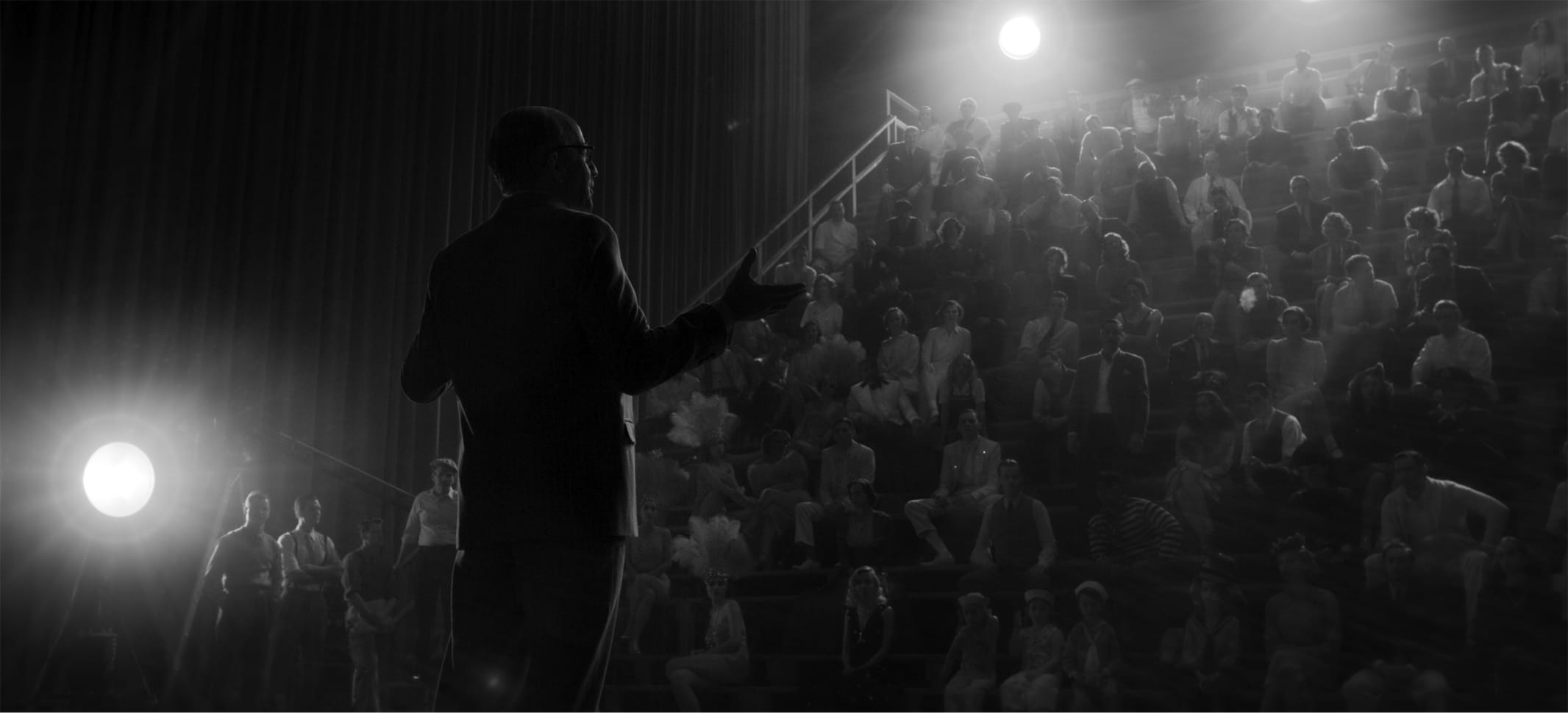In a shot from the film, we see how the scene above translates to a black-and-white experience. The spotlights around the theater are like small suns.