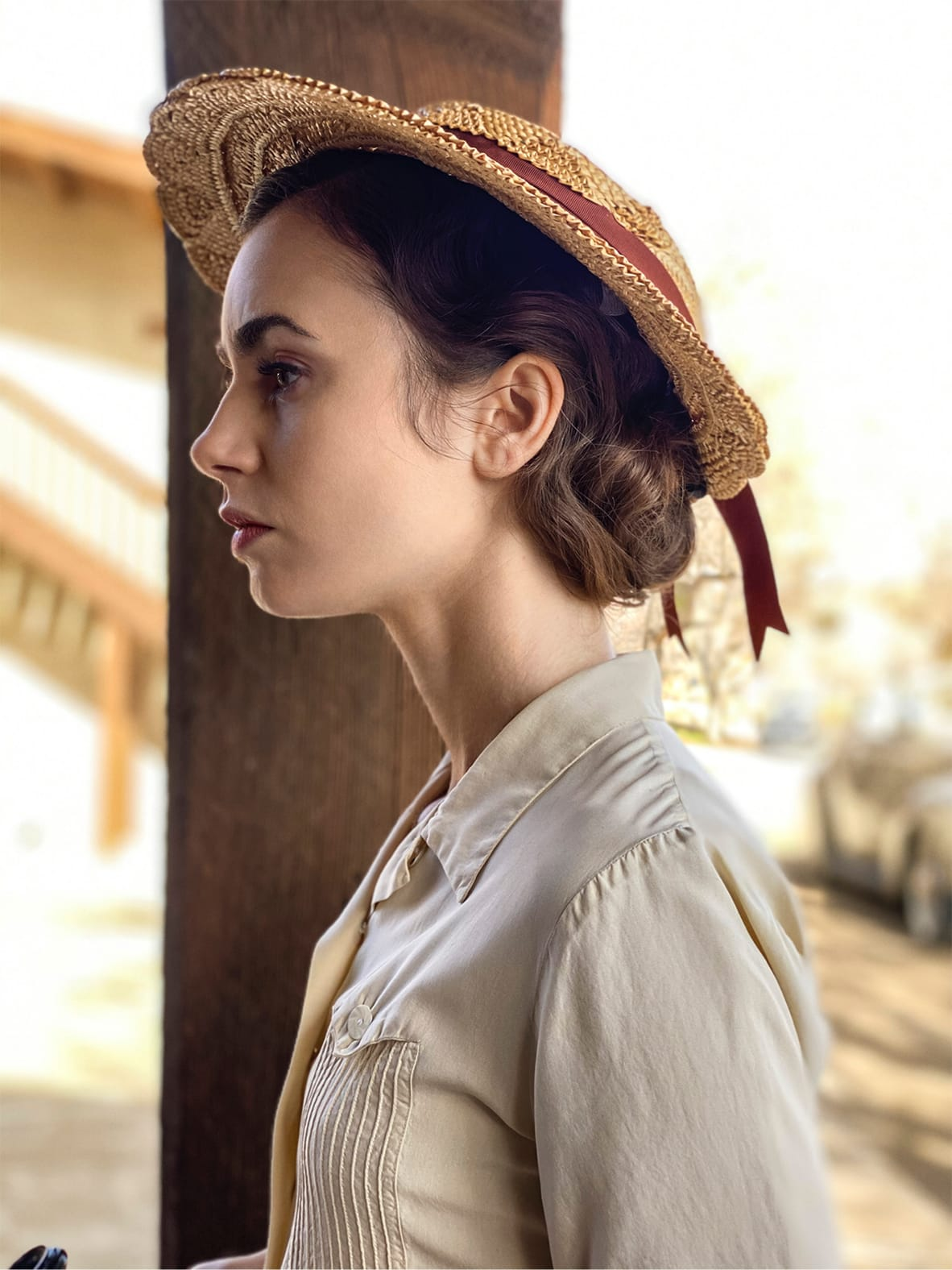 Lily Collins in character wearing a cream blouse and tan sunhat. She's pictured in the desert light, everything browns and yellows.