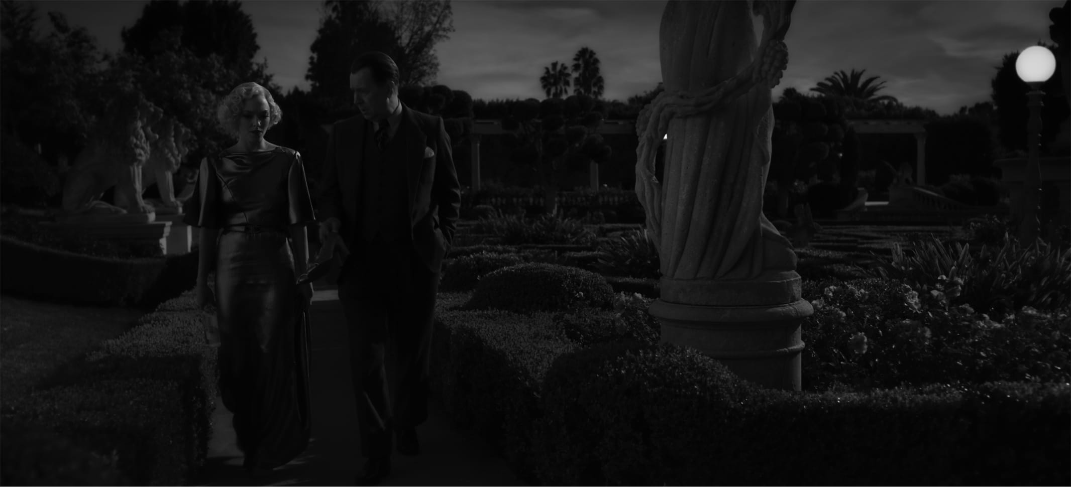 In a shot from the film, we see how the vibrant colors from the image above translate to a black-and-white experience. Light and shadow play off of Seyfriend's shimmering dress and around statues and greenery on the grounds.