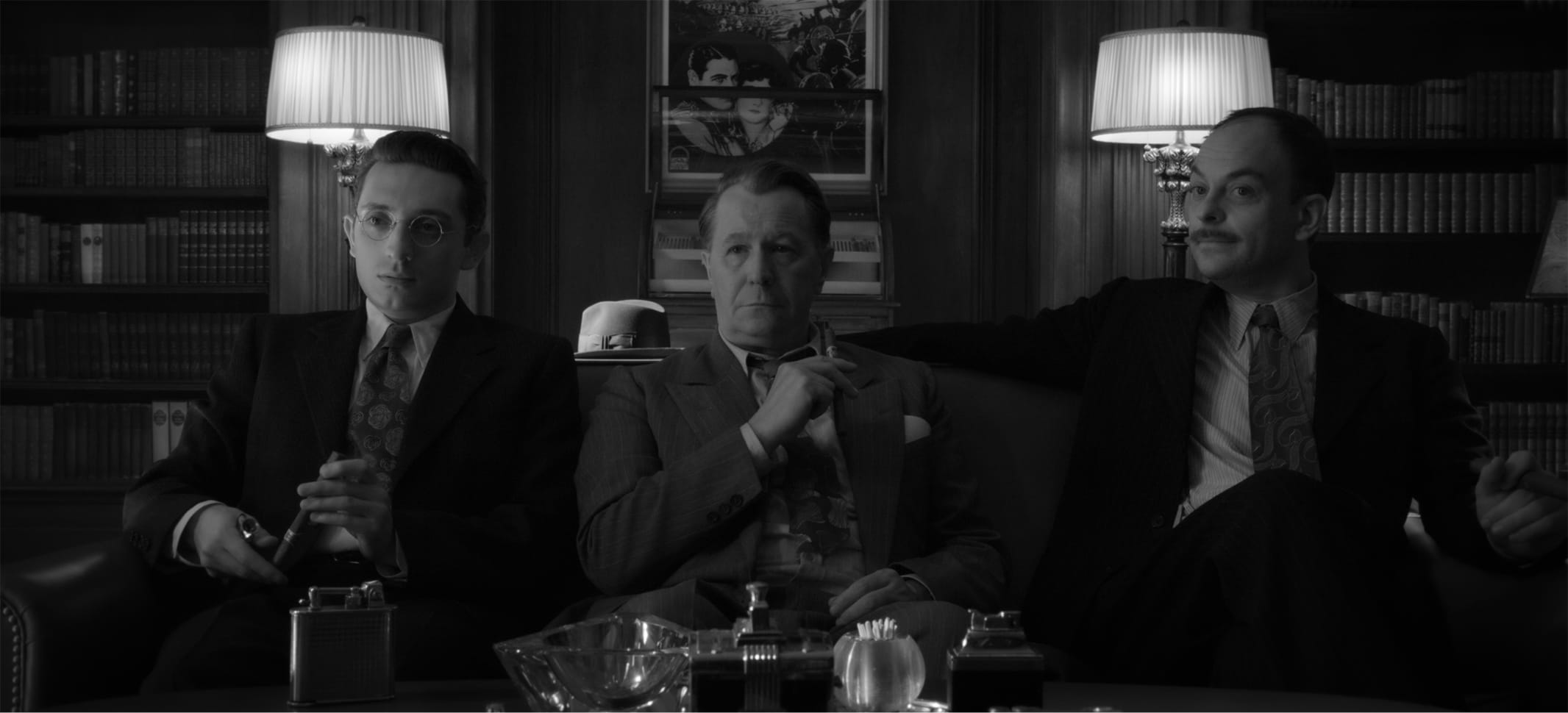 In a shot from the film, we see how the scene above translates to a black-and-white experience. Romano, Oldman, and Hecht are pictured on one of the office couches, framed by two of the office's three lamps.