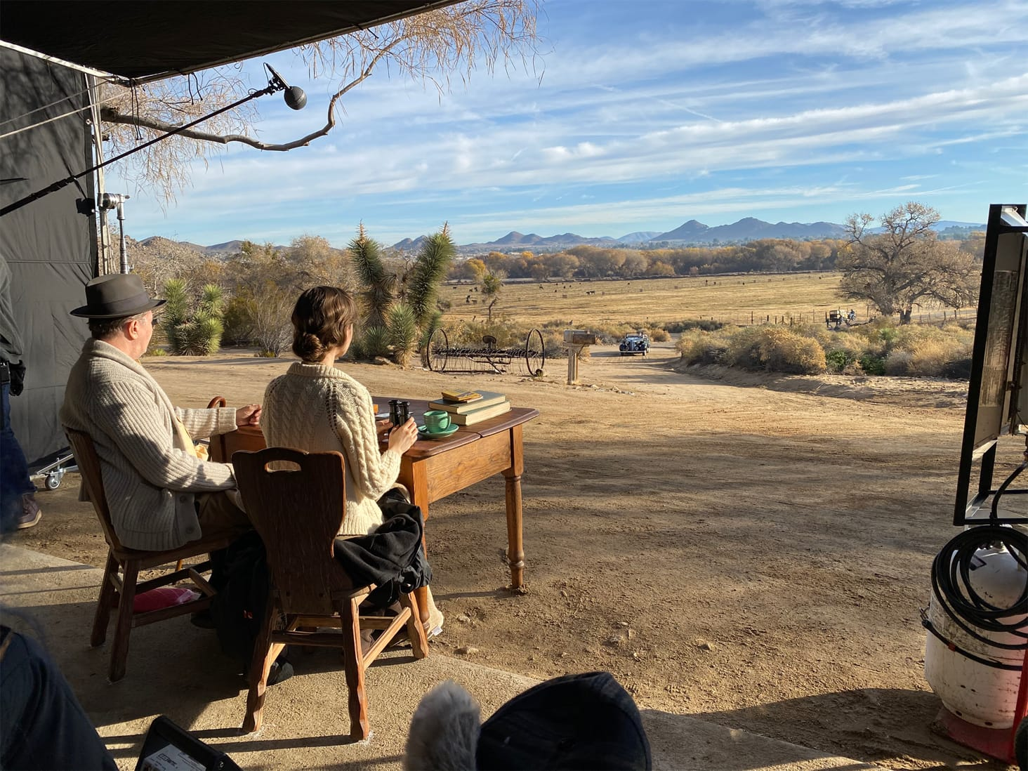Oldman and Lily Collins in character on the set of Mank. The pair are seated at a table, gazing out at the backdrop that serves as the California desert. The sky is a bright blue and the expanse in front of them is a dusty yellow.