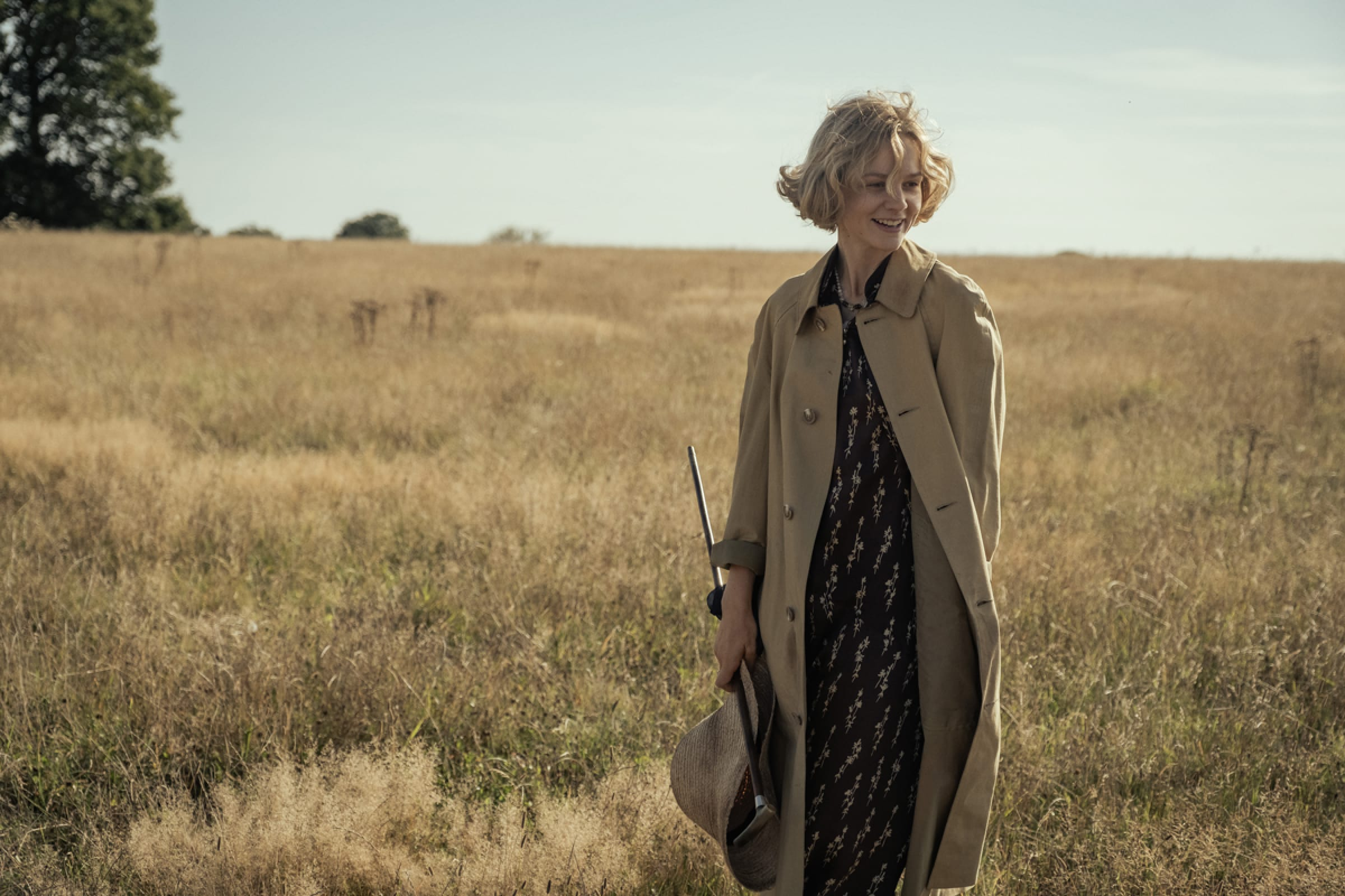 Edith wears a beige trench coat and holds a cane. Her hair blows in what one can only imagine is a sweet and gentle breeze.