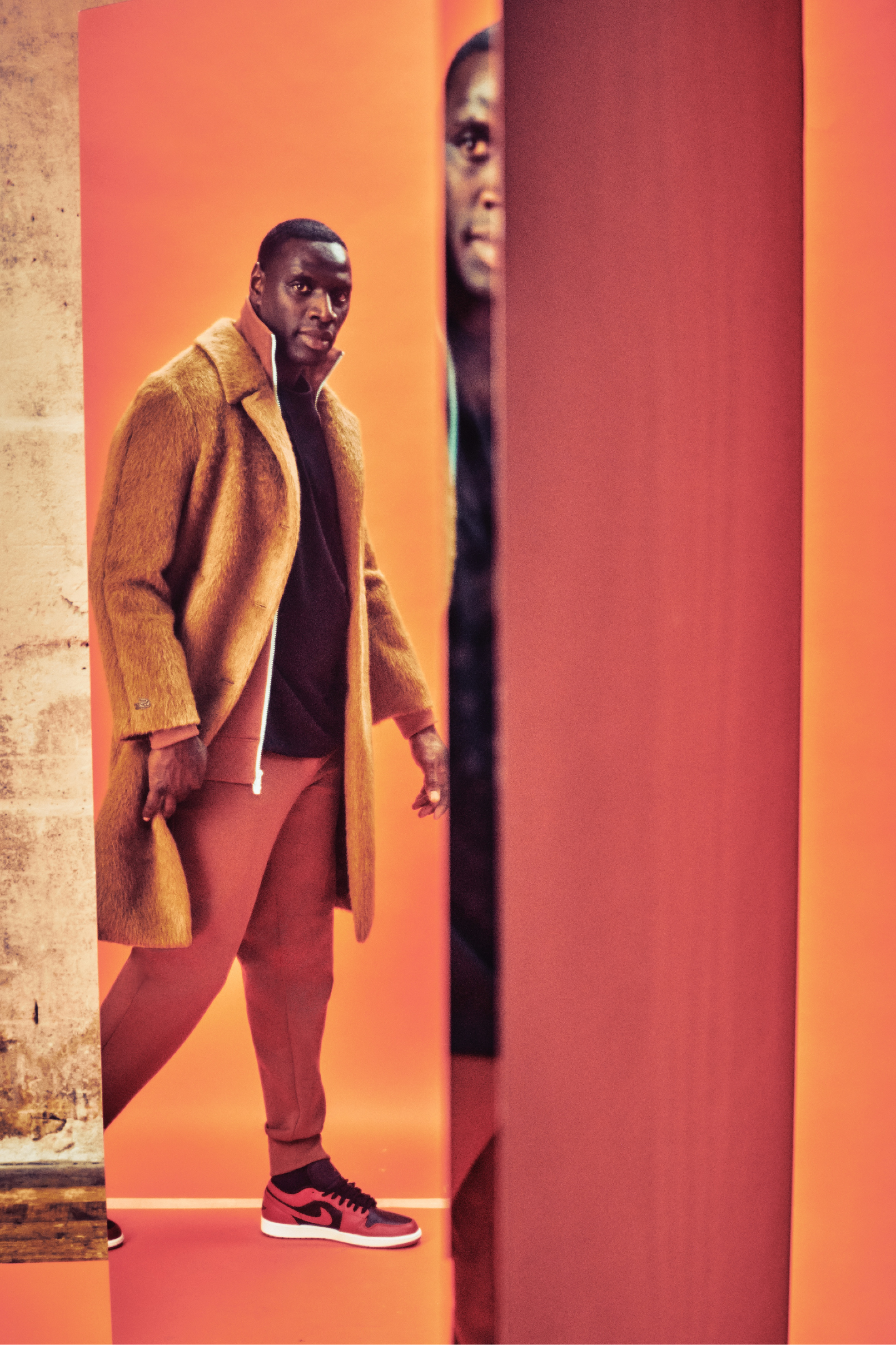 More reflections of Sy, this time in a long orange-brown coat and red Jordan 1s.