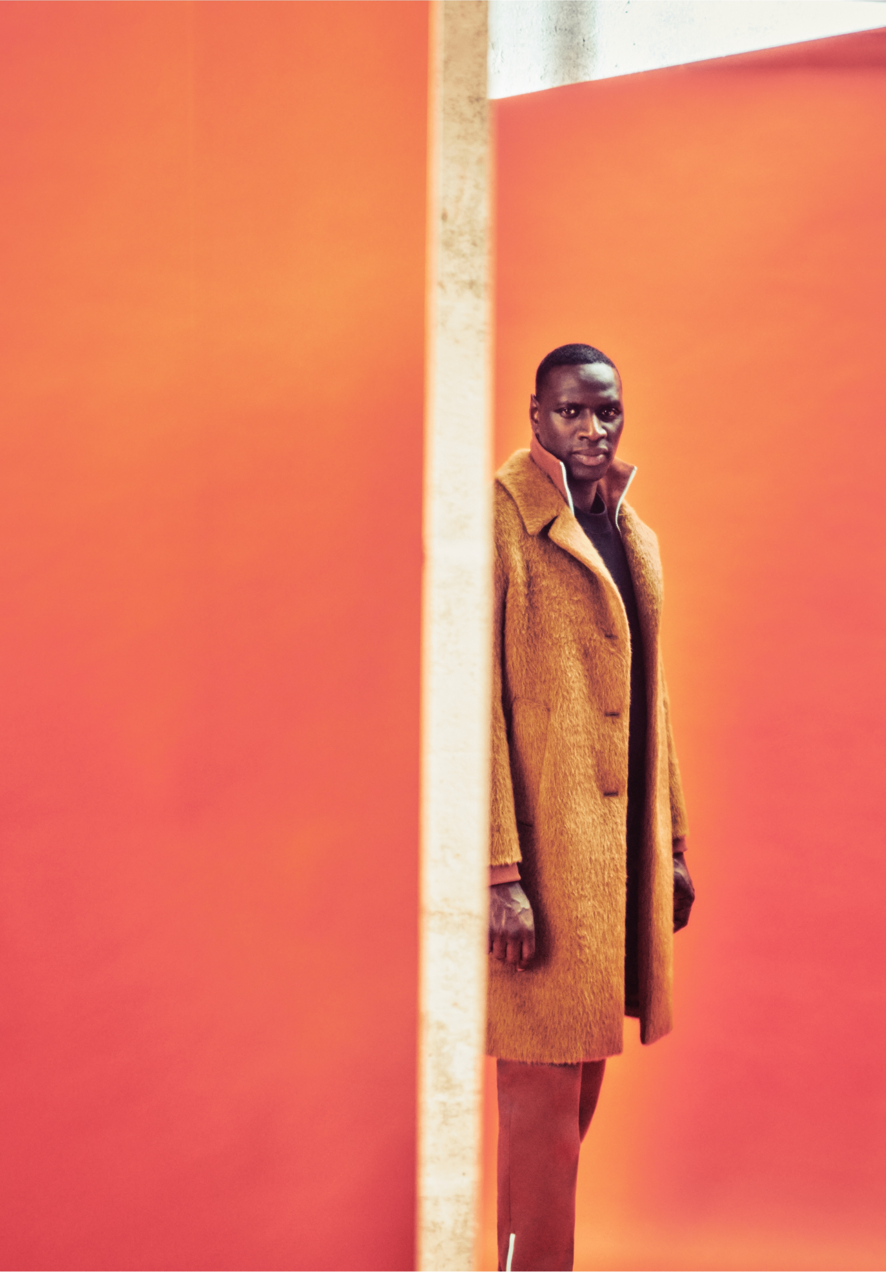 Sy, in a long orange-brown coat, turns to camera.