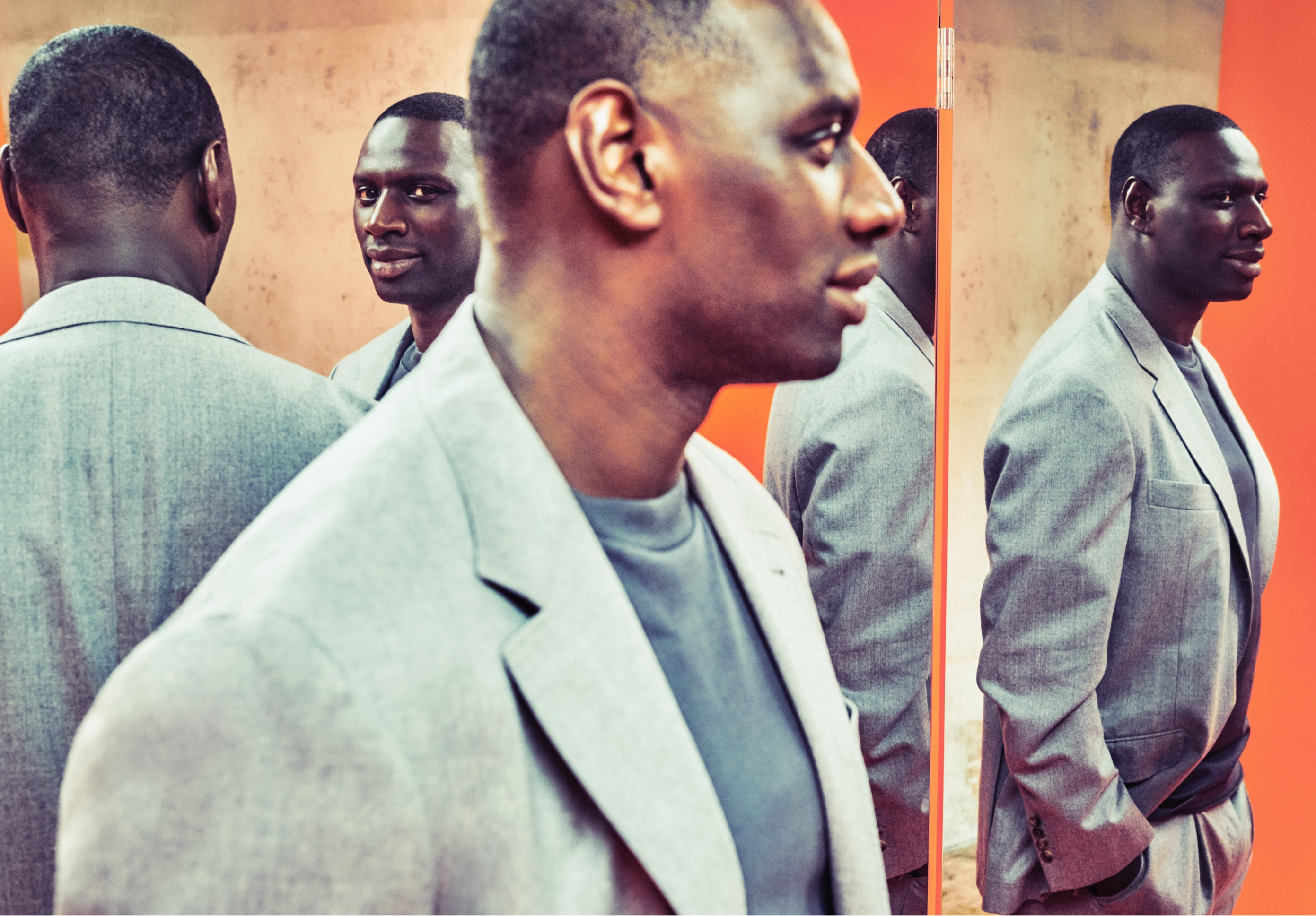 Reflections of Omar Sy populate this brightly colored image. The actor is pictured in a light-colored blazer, which pops against a strong orange background.