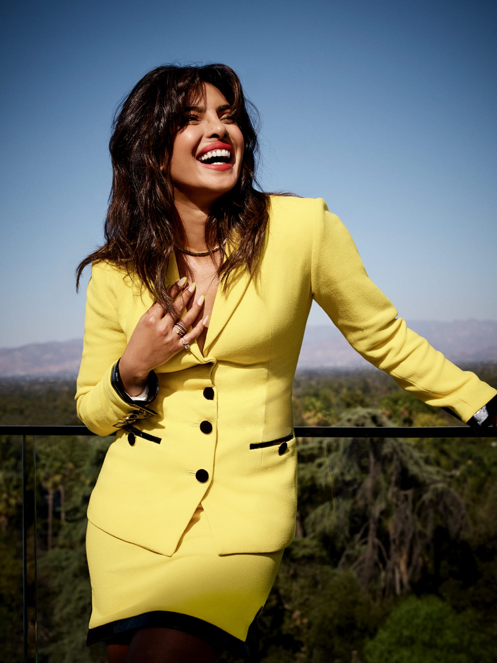 Priyanka Chopra Jonas poses, laughing, on a balcony, with Hollywood behind her. She sports a bright yellow suit with black buttons.
