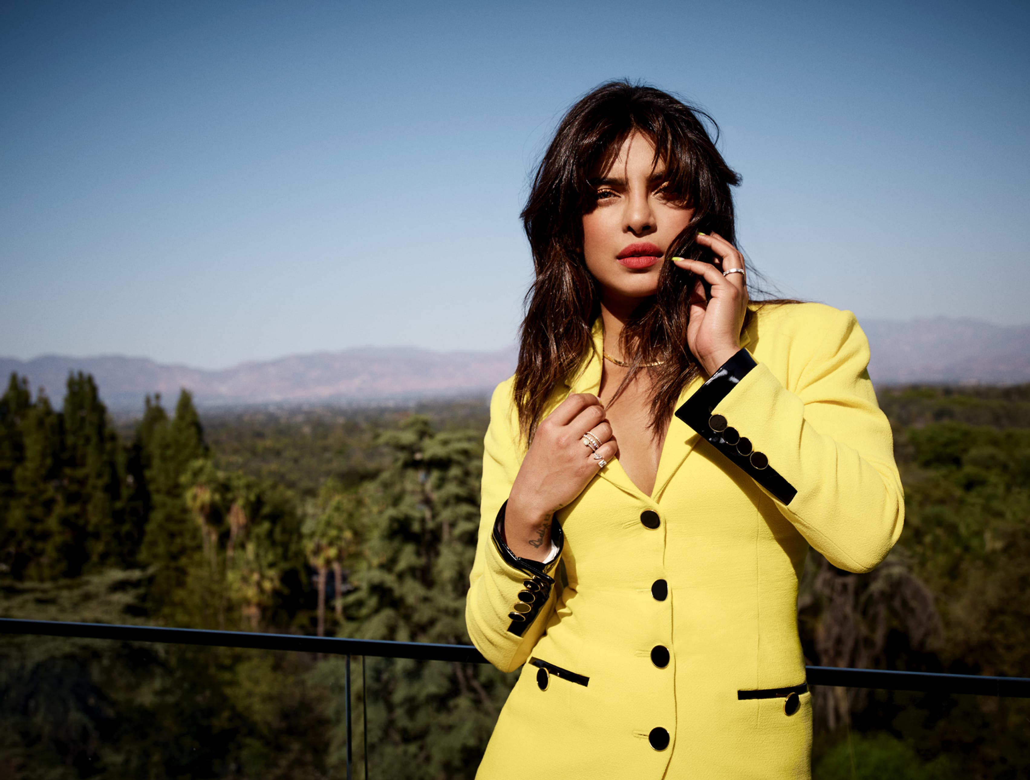 Priyanka Chopra Jonas posed again in her yellow suit, Hollywood as her backdrop. She holds one hand to her hair while the other gently grasps her lapel.