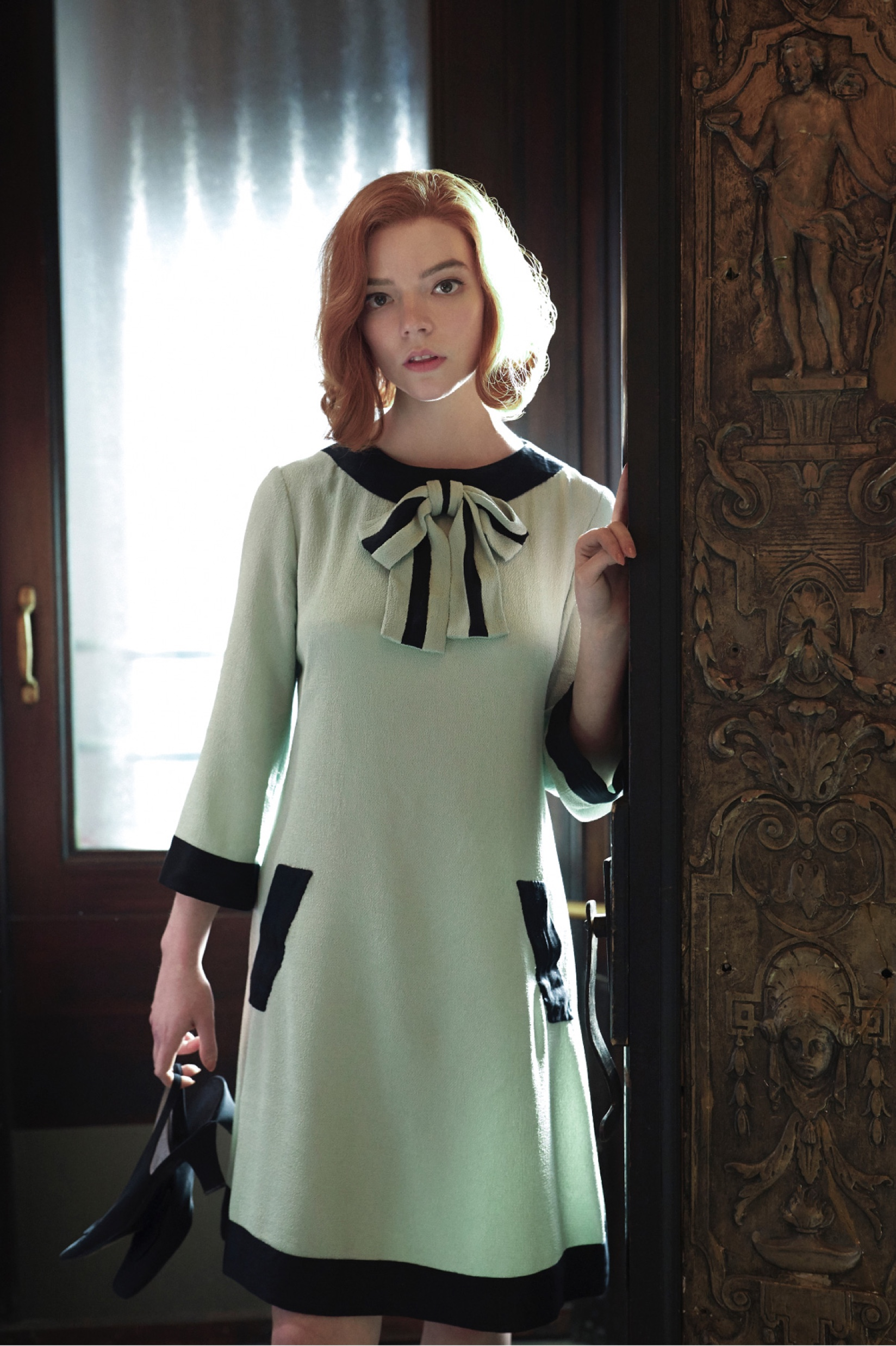 Beth stands in a doorway, heels in hand, wearing her iconic bow dress.