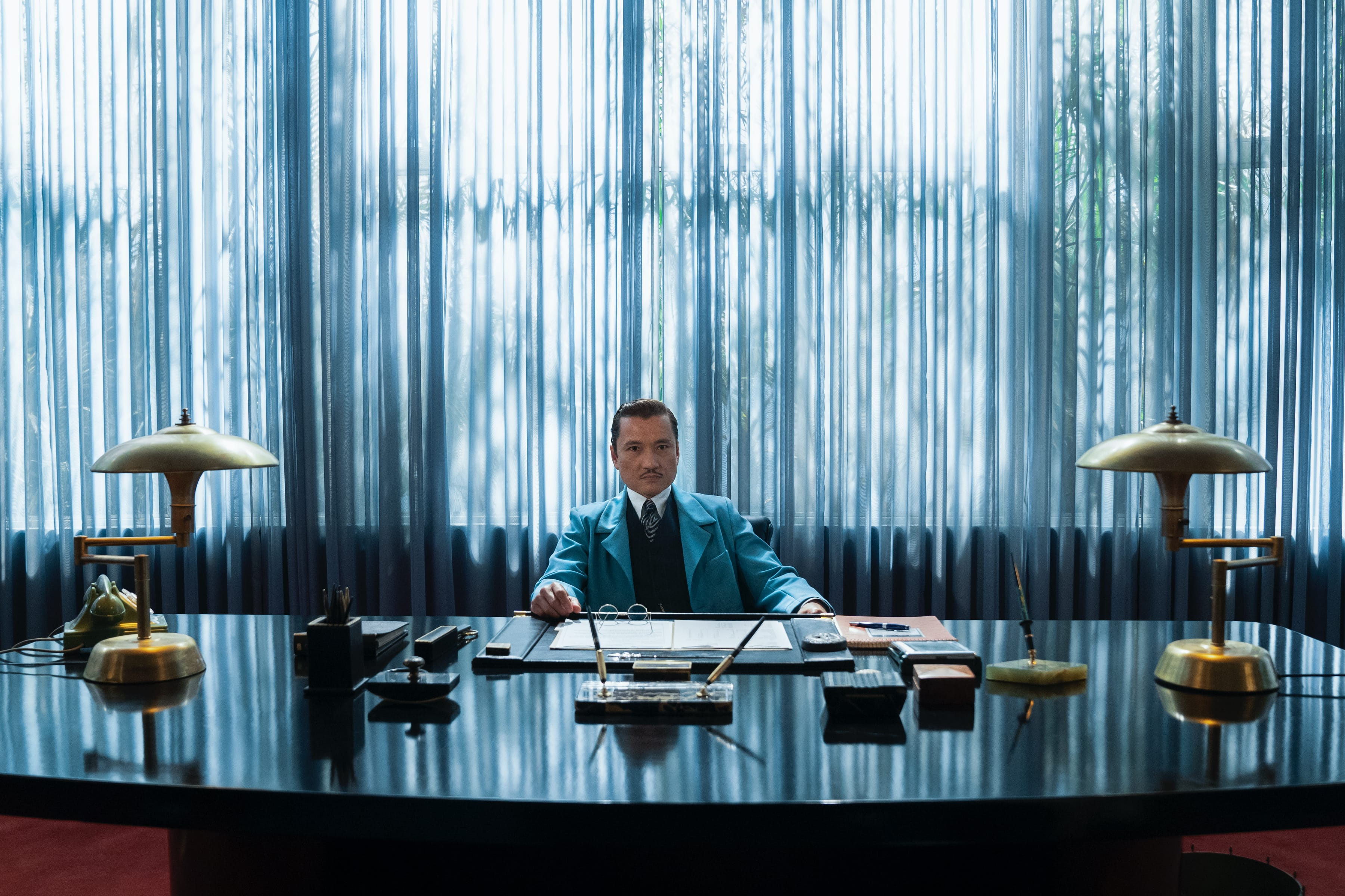 Dr. Hanover is stationed behind an imposing desk in his oppressively blue office.