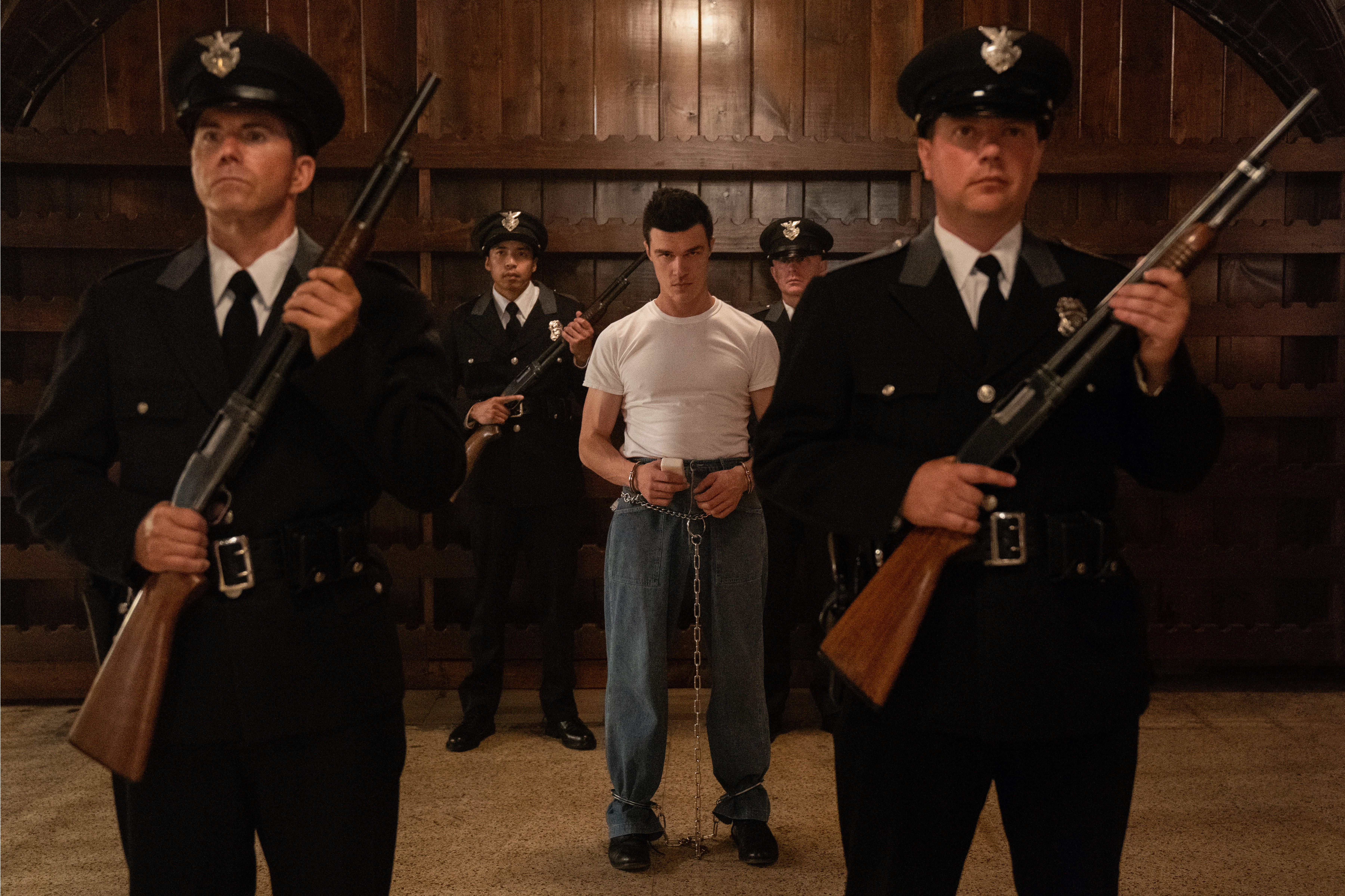 Edmund Tolleson looks deranged in a white muscle-shirt, surrounded by rifle-carrying guards.