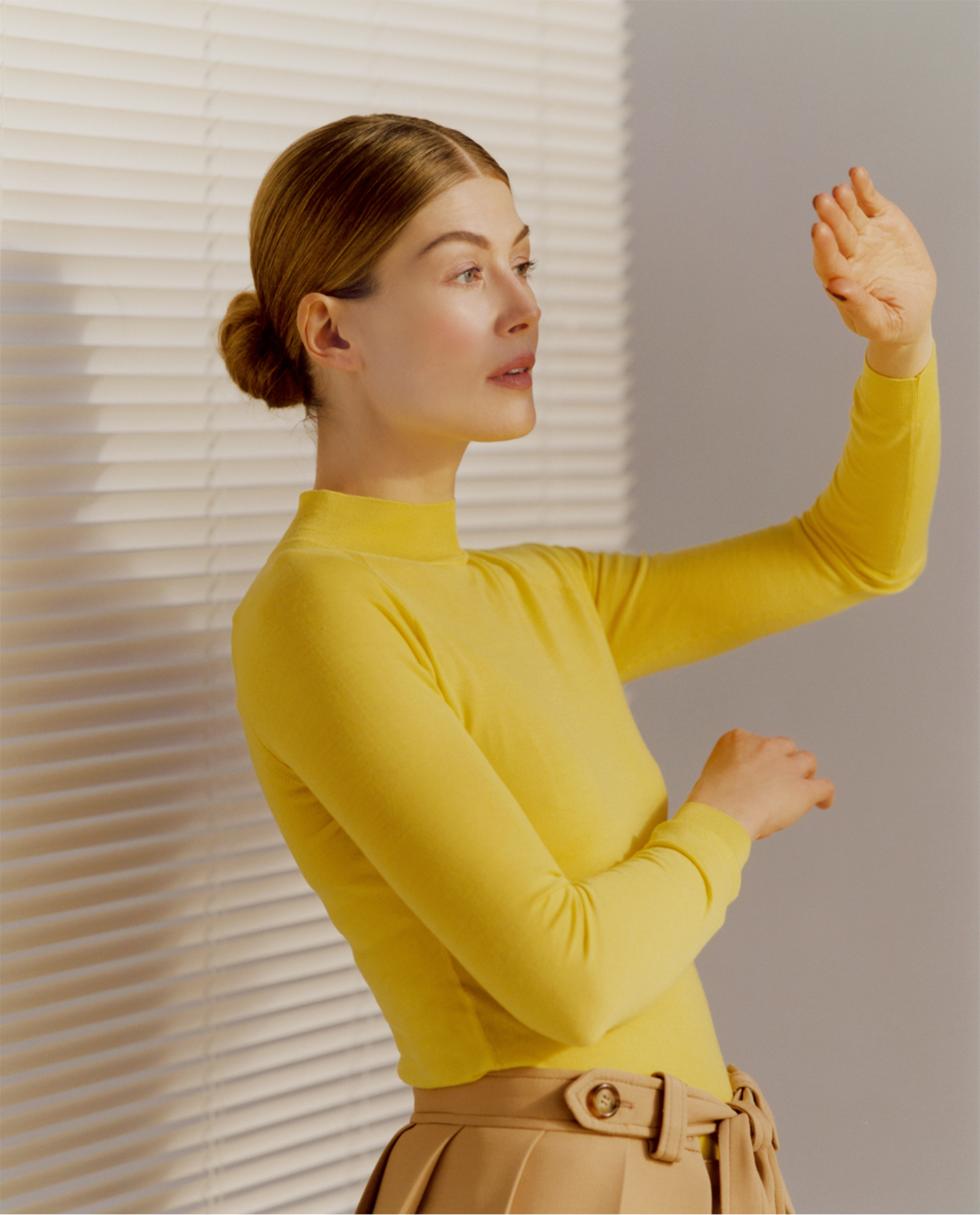 Rosamund Pike, posed in front of closed venetian blinds, wearing a bright yellow fitted turtleneck and beige trousers. She holds a hand up against the light pouring in from an unseen source in front of her.