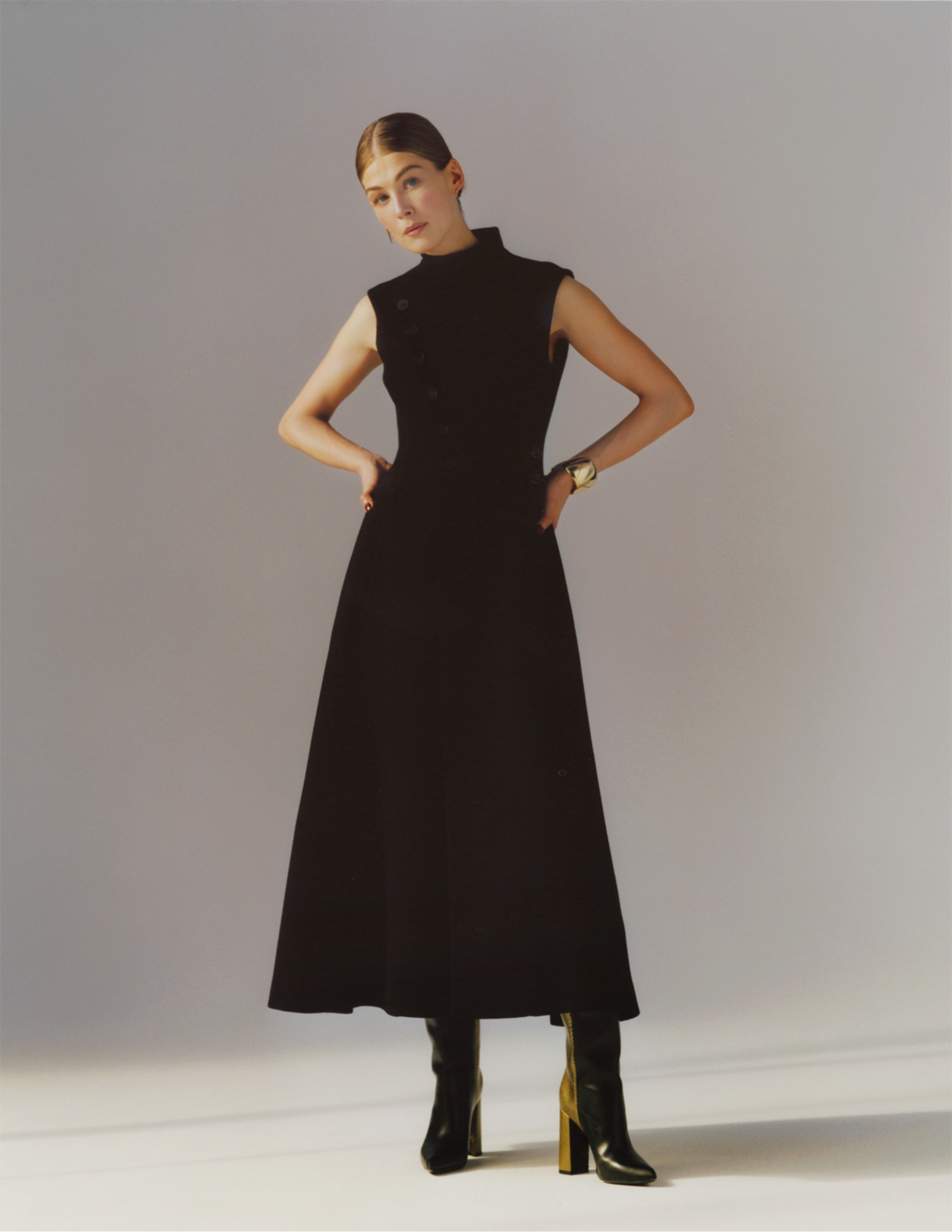 Rosamund Pike poses against a gray and white backdrop in a high-neck, long black dress and heeled black boots, her hands on her hips.