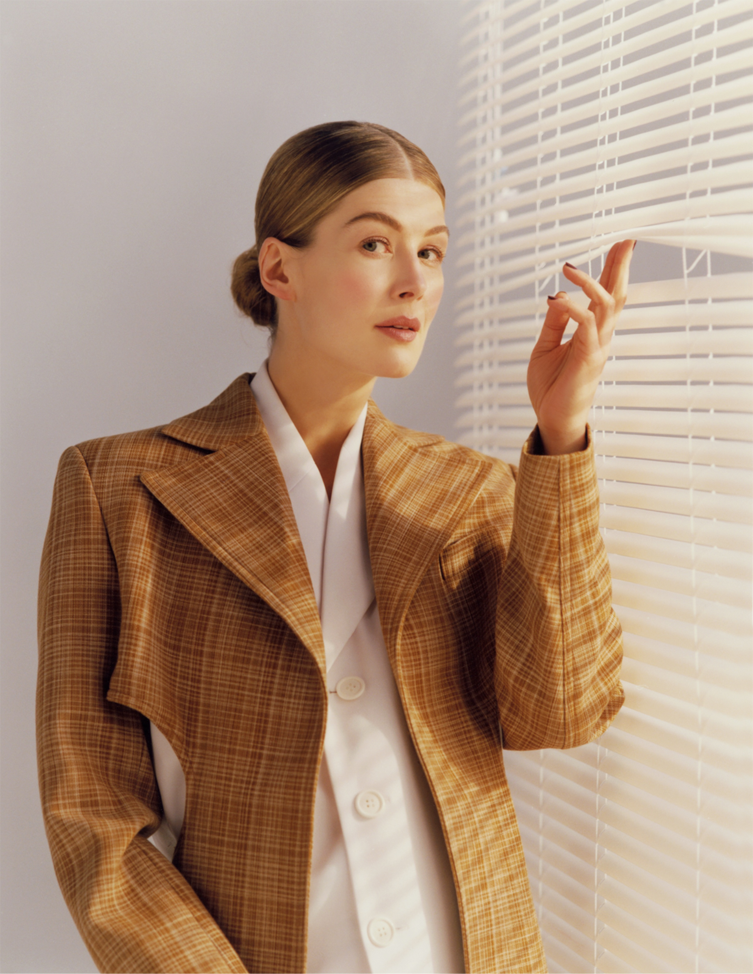 Rosamund Pike poses in a checkered jacket and white shirt. She looks askance at the camera as she uses two fingers to lift up a panel on a set of venetian blinds.