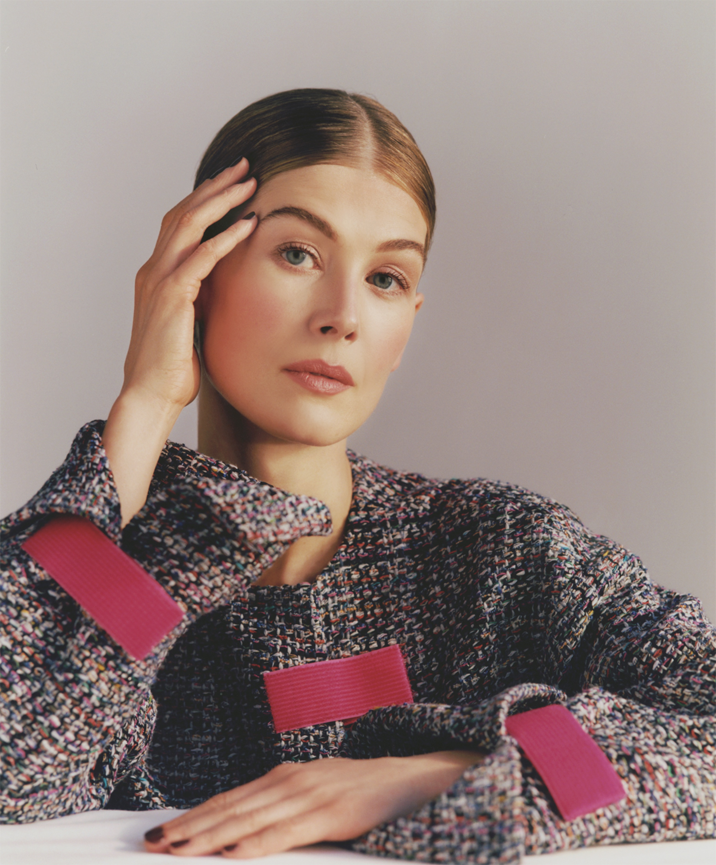 A portrait of Rosamund Pike wearing a tweed jacket with red accents on the cuffs and pocket. Her hair is pulled tightly back and parted down the center. She leans her head delicately on one hand.