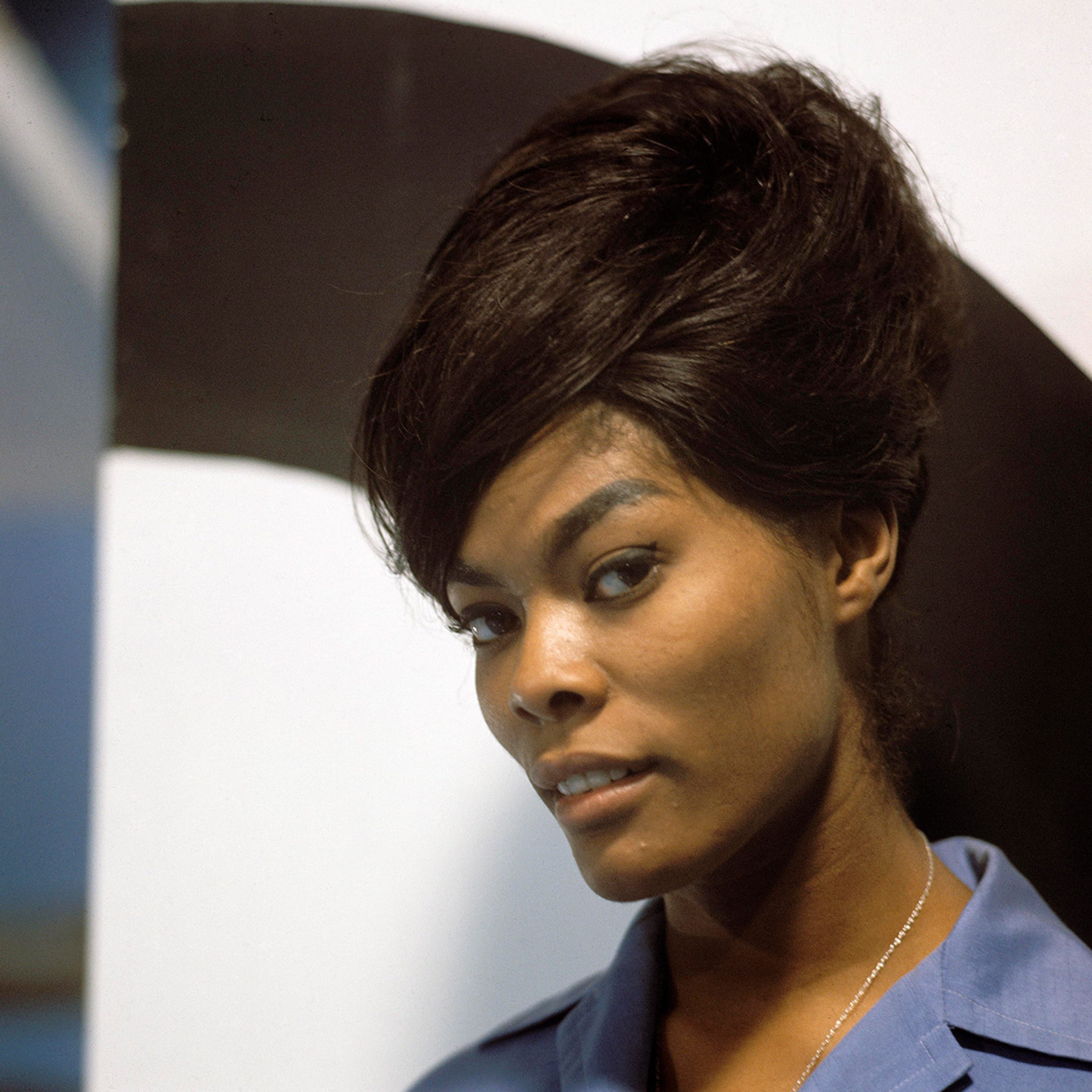Singer Dionne Warwick looks at the camera. Her hair is in a beehive style and her blue shirt collar is visible.