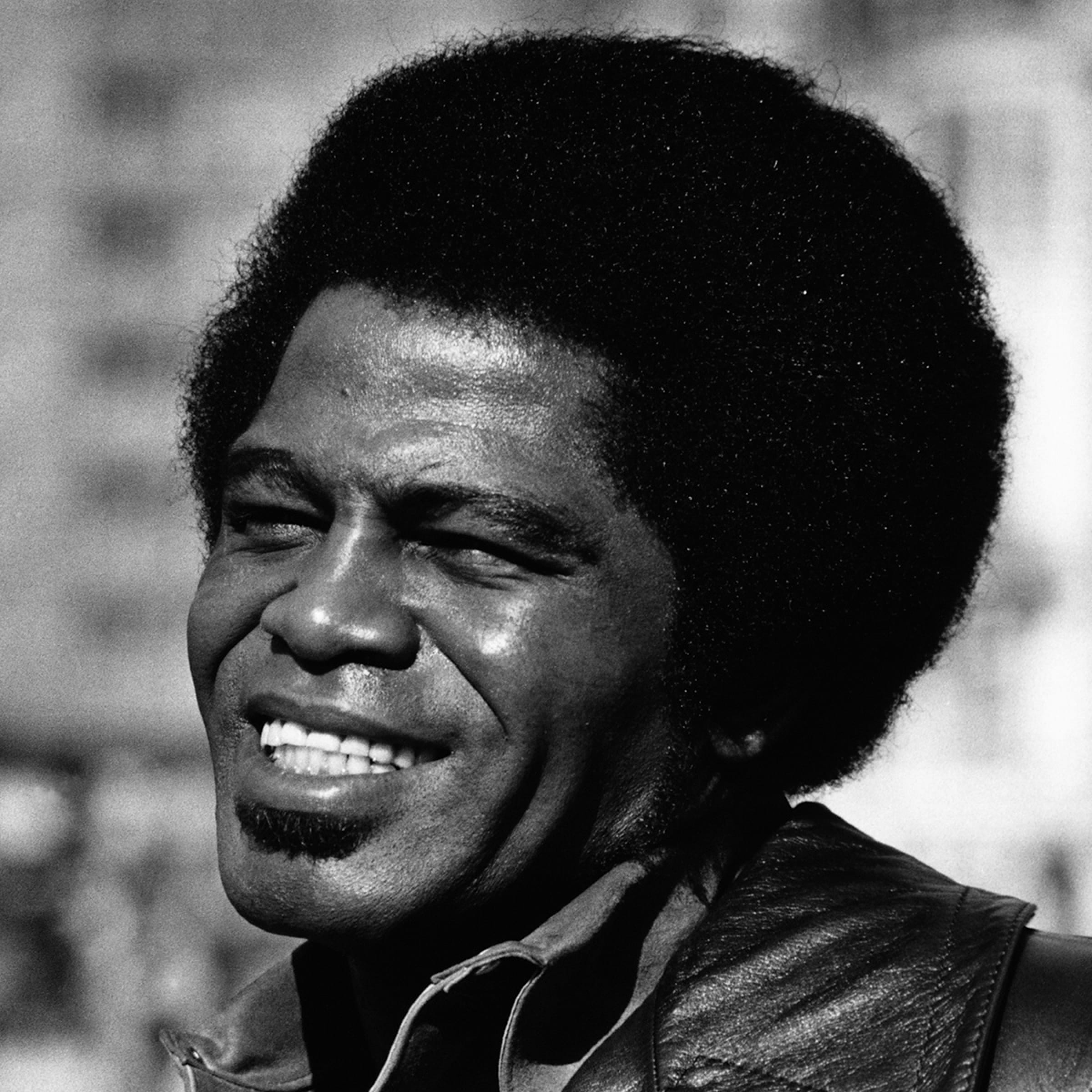 James Brown pictured in a black-and-white photo. He smiles, eyes squinting against the sun, in front of a blurred cityscape.