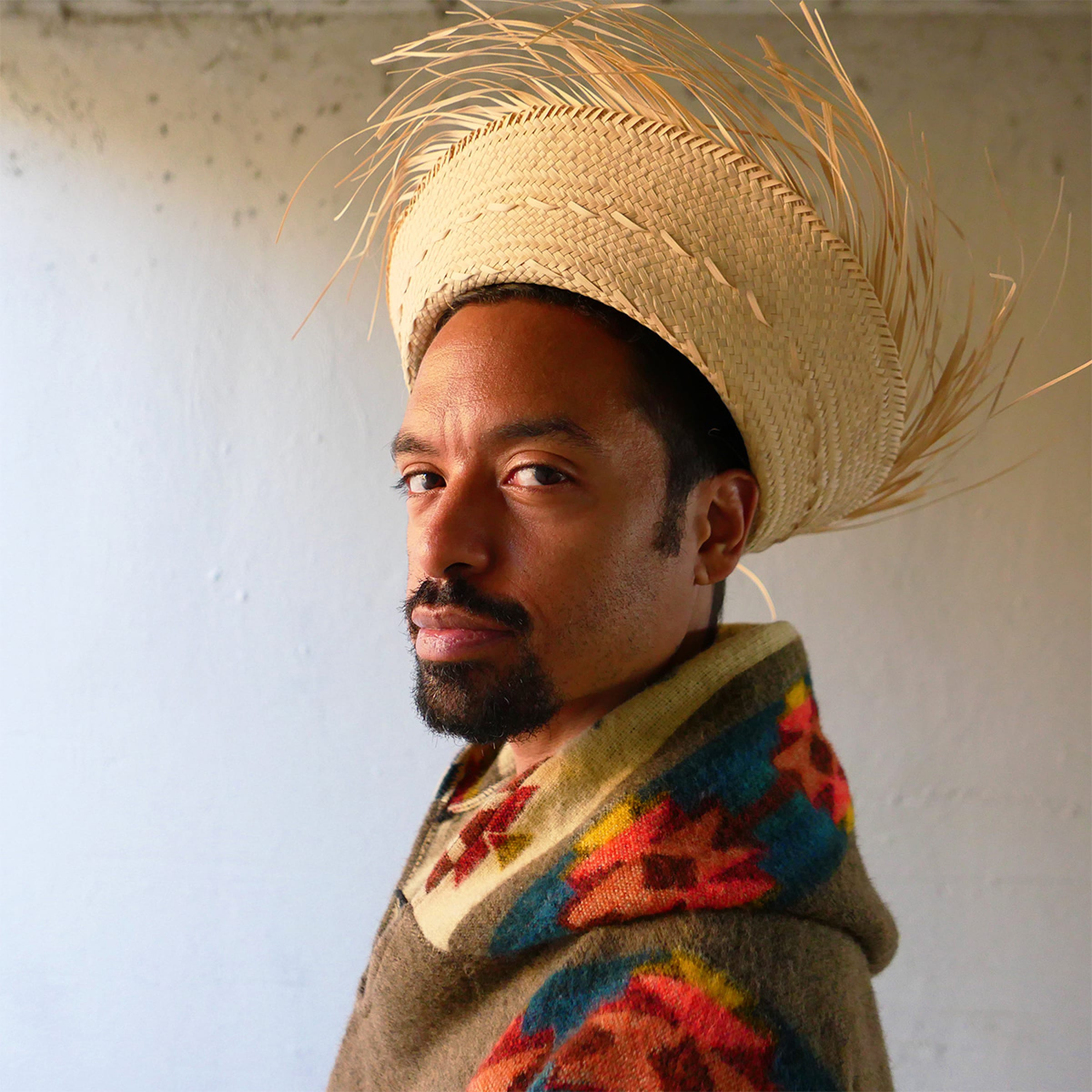 Frankie Reyes turns towards the camera, wearing a large straw hat and a woolly green sweater with a tribal print of orange, blue, yellow, and burgundy.