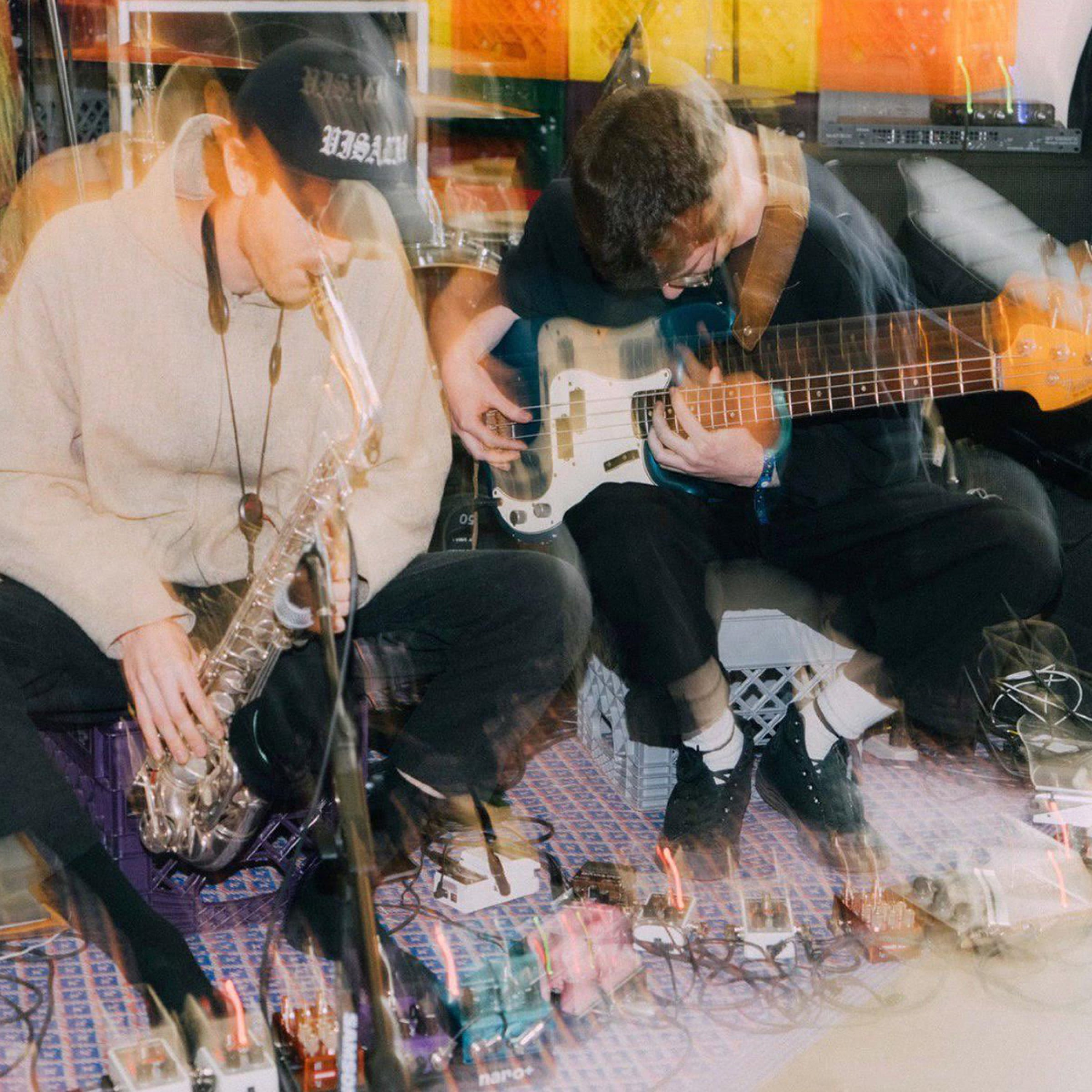 A blurry image of Sam Gendel and Sam Wilkes, playing their guitar and saxophone above a row of pedals.