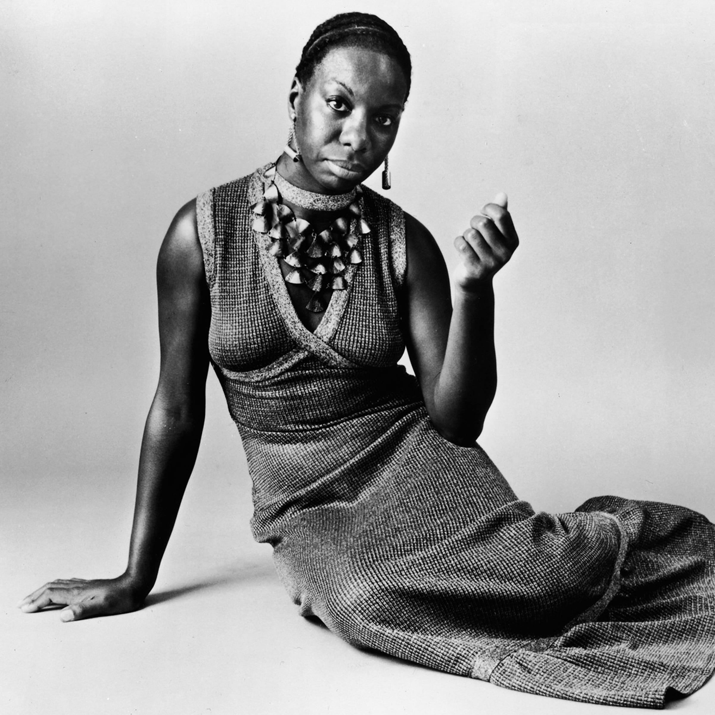 This studio portrait shows American pianist and jazz singer Nina Simone reclining on the floor circa 1968. She's wearing a necklace with dangling tassels and a v-neck cut long dress.