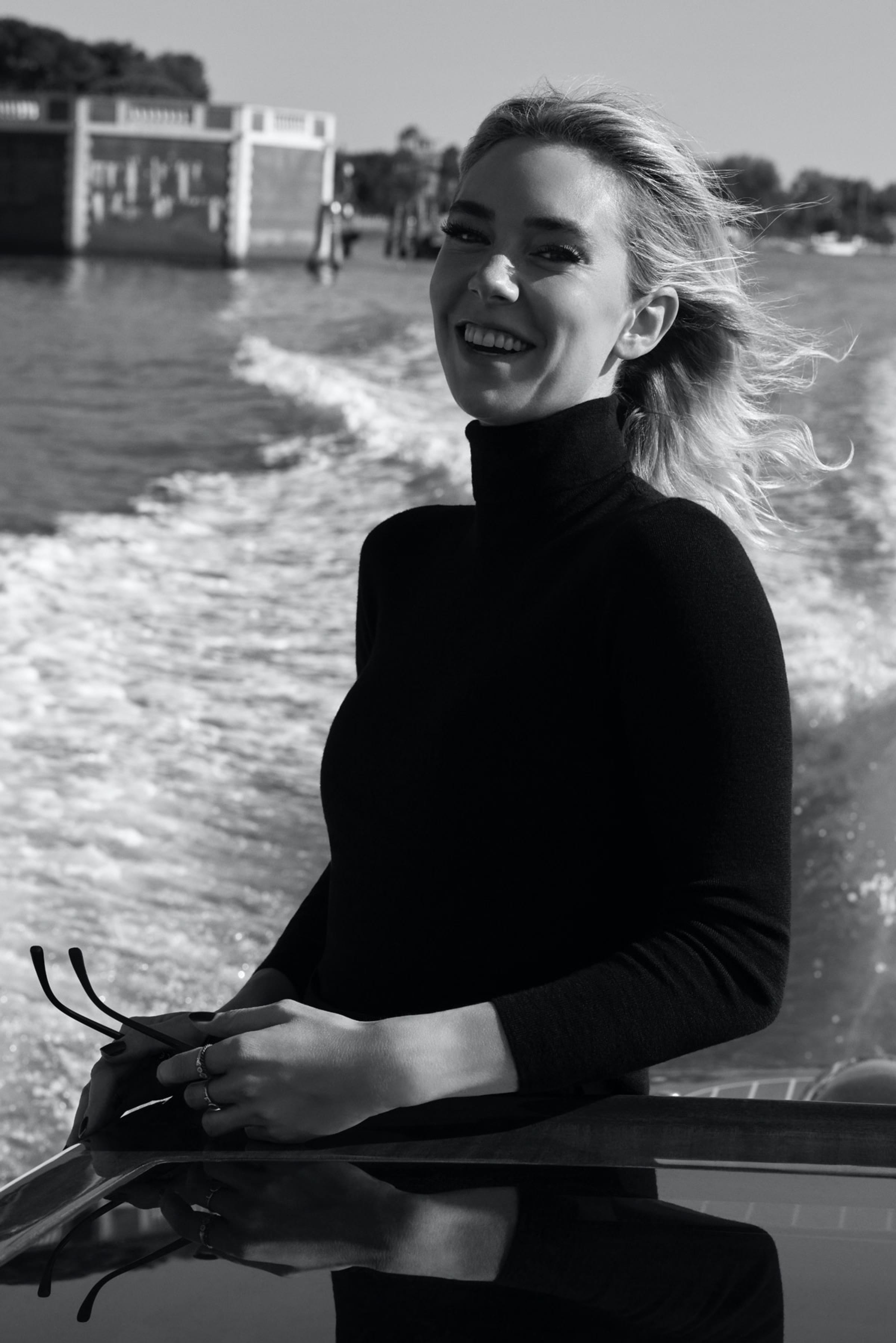 Vanessa Kirby smiles as she stands on a boat, her hair blowing in the wind.