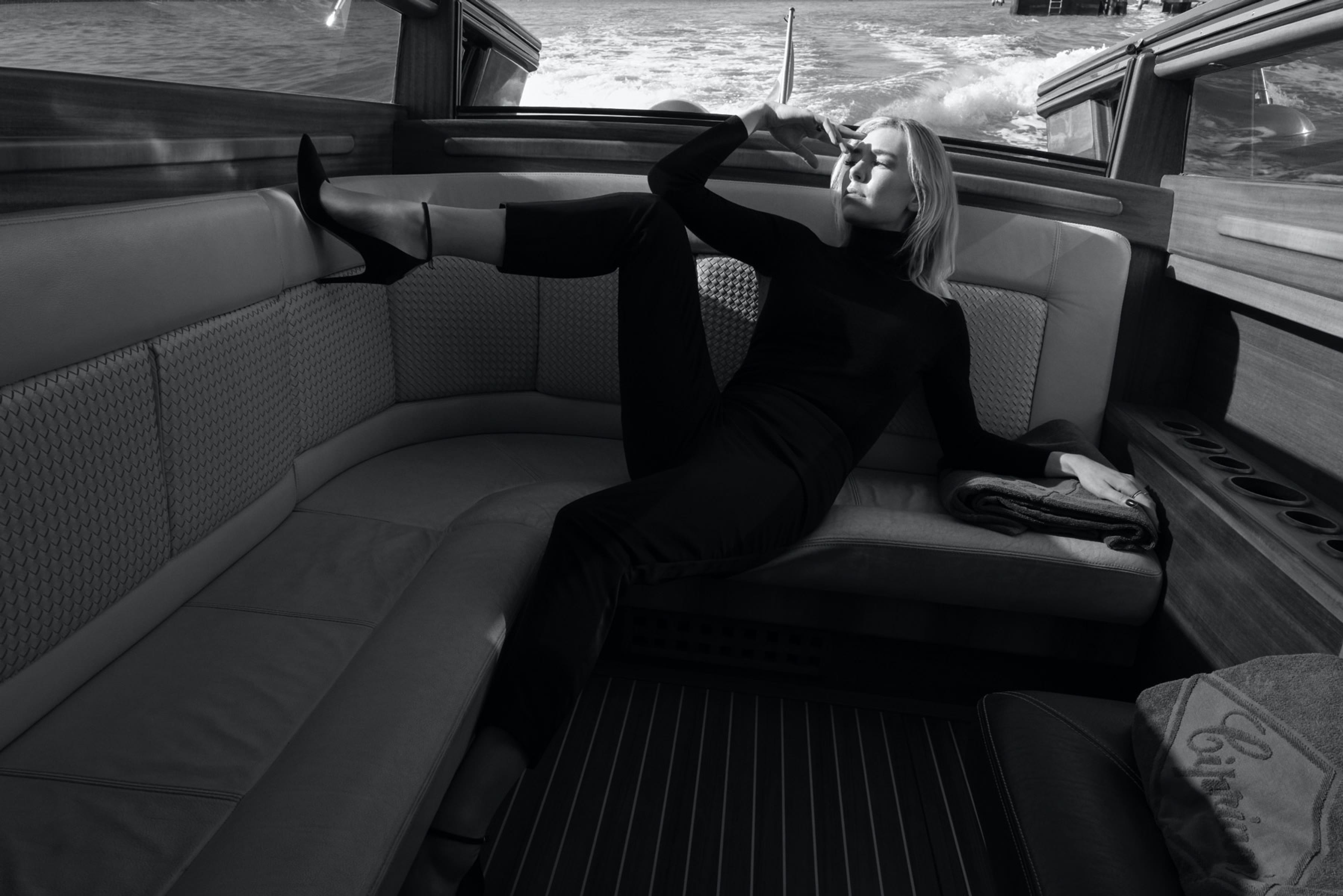 Vanessa Kirby lounges inside the boat, pressing a black stiletto against the cream-colored seats.