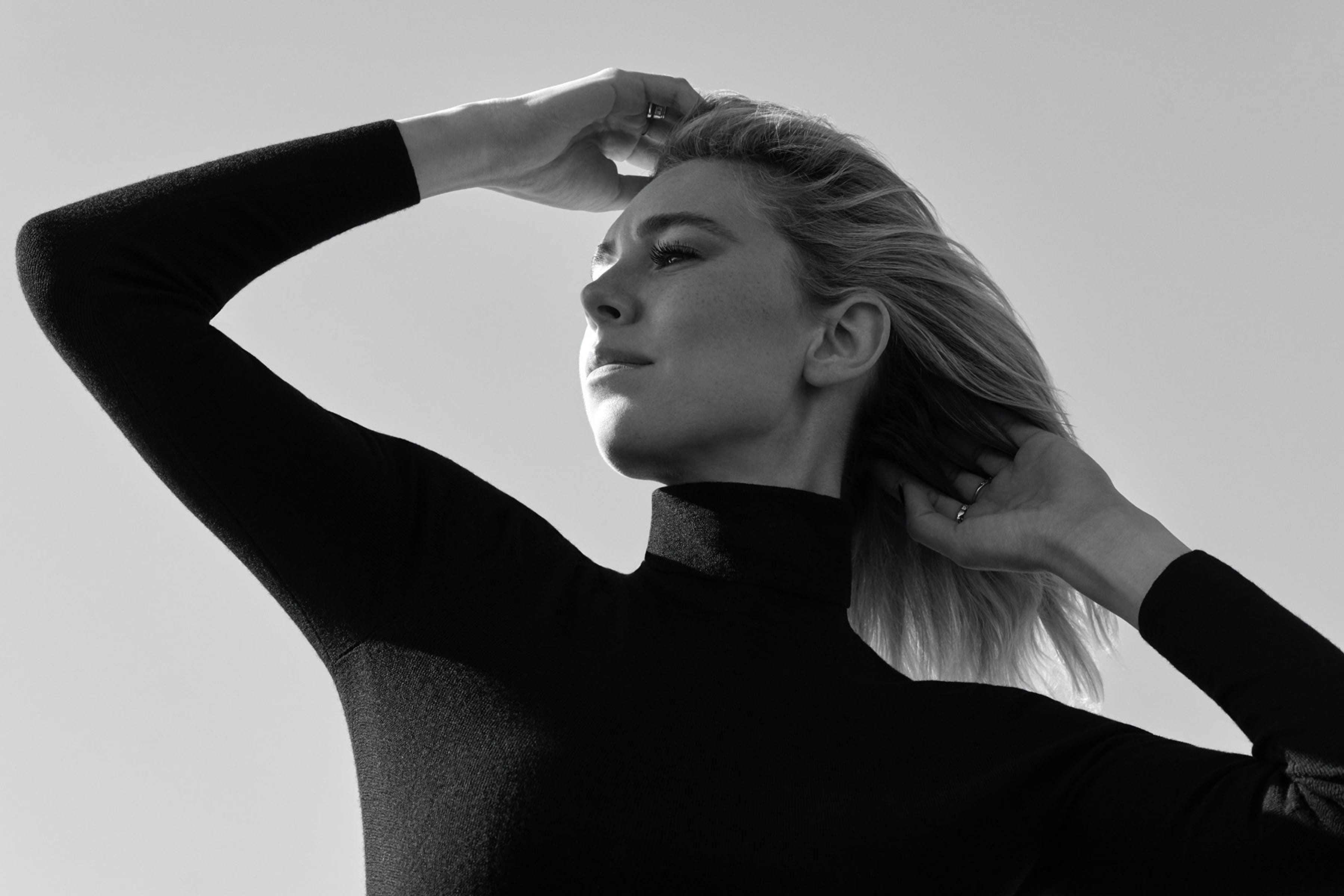 Vanessa Kirby poses in profile, arms akimbo. The sun hits her face and her hair blows in the breeze.