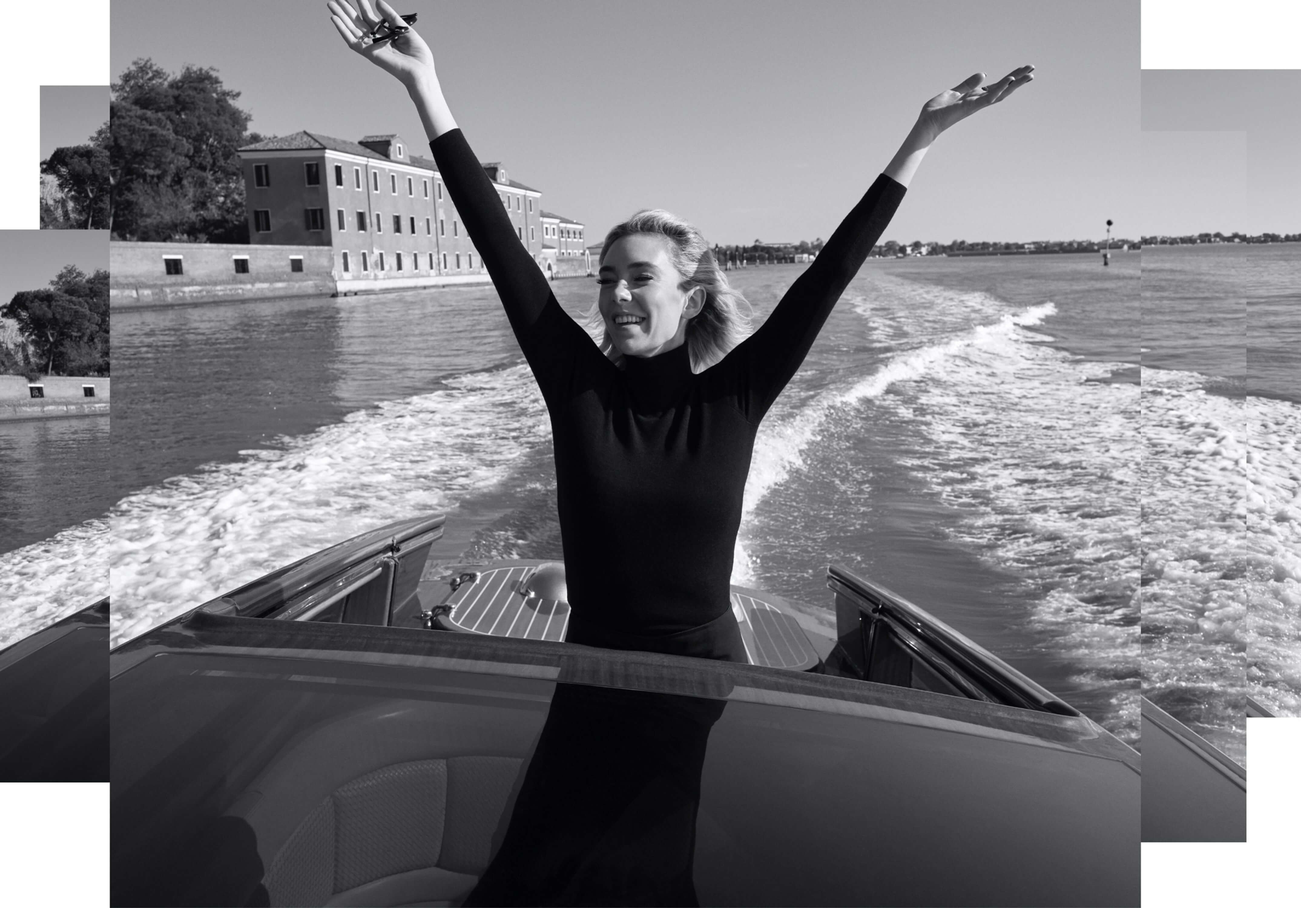 Vanessa Kirby sails through the waters of Venice in this black-and-white shot. She wears a chic black turtleneck and throws her hands to the sky in a gesture of joy.