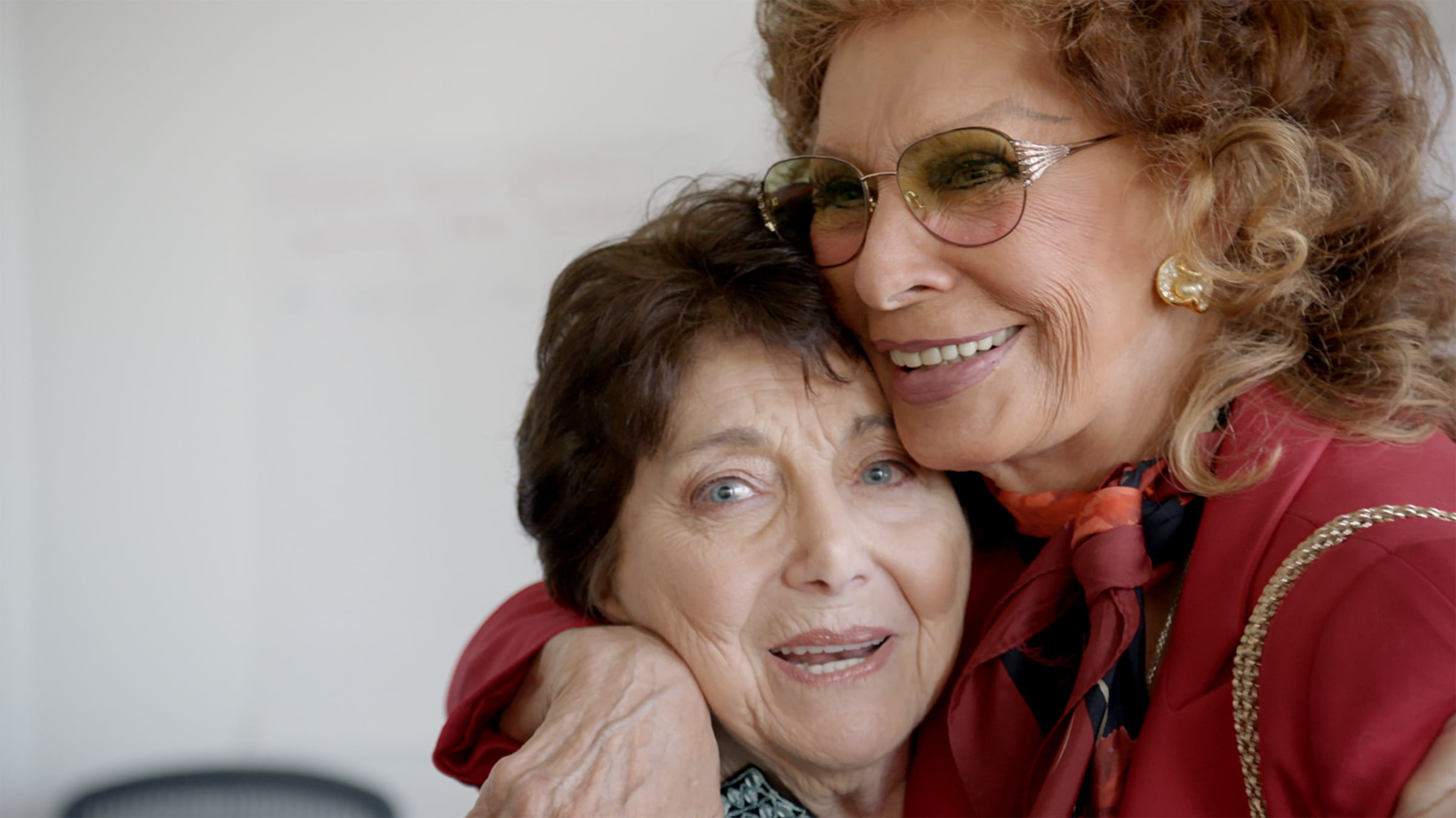 A close-up of Kulik and Loren as they embrace. Kulik looks straight to camera. Loren wears a red blazer, scarf, and sunglasses.