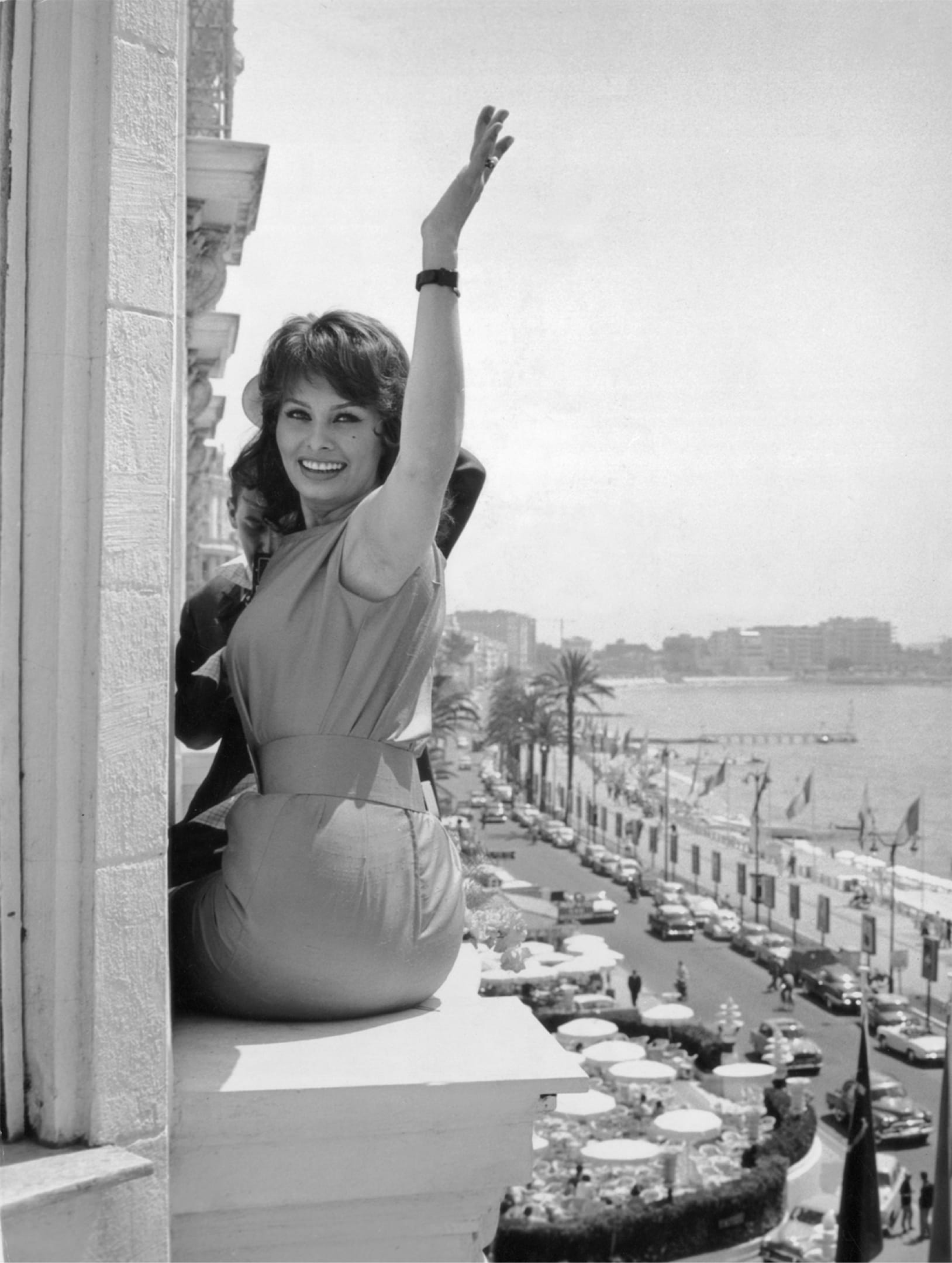 A black-and-white photo of Sophia perched on her hotel windowsill above Cannes