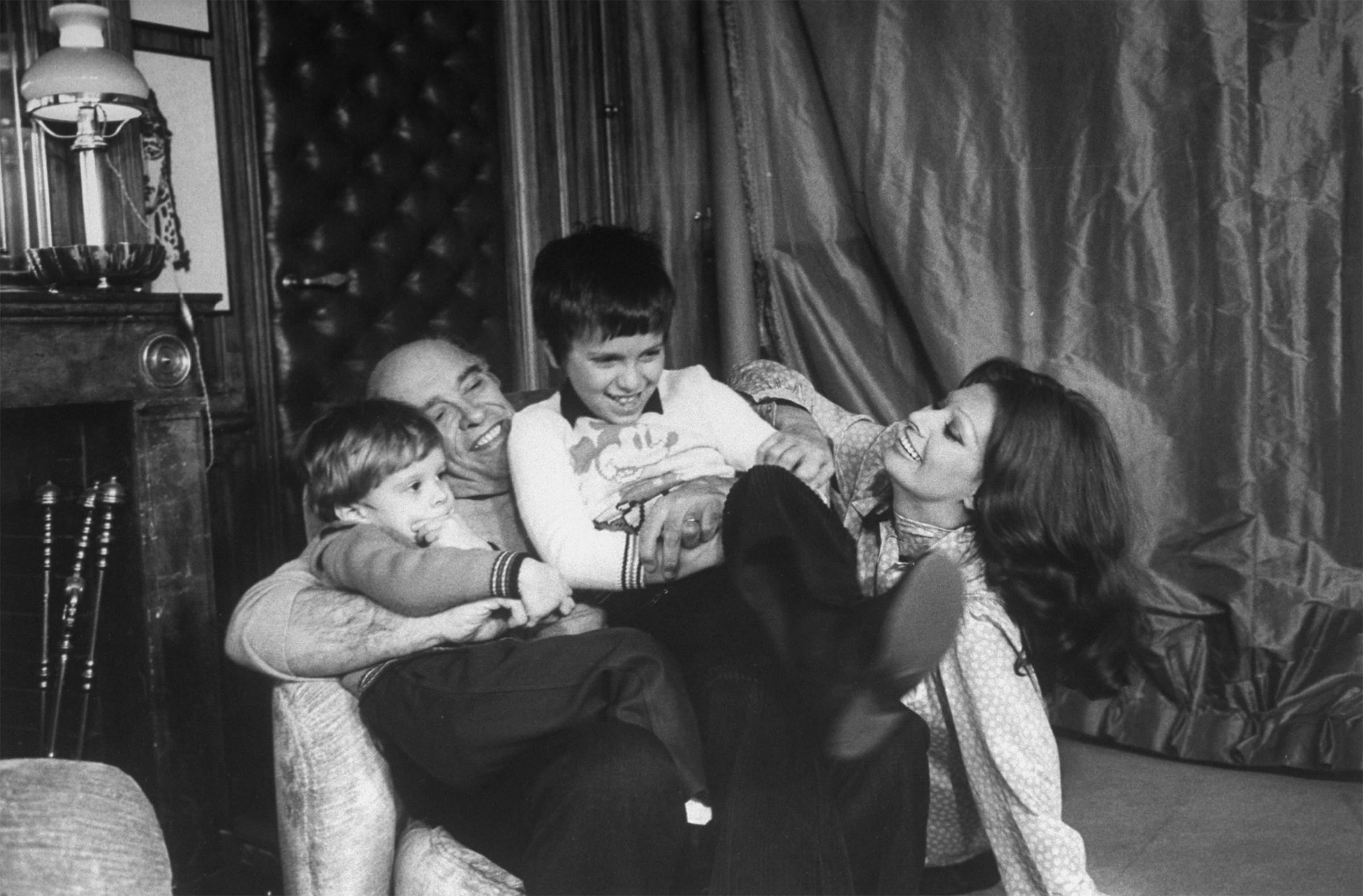 In this playful old photograph, Carlo Ponti sits in an armchair, holding his two young children, while Loren smiles at them from her seat on the floor.