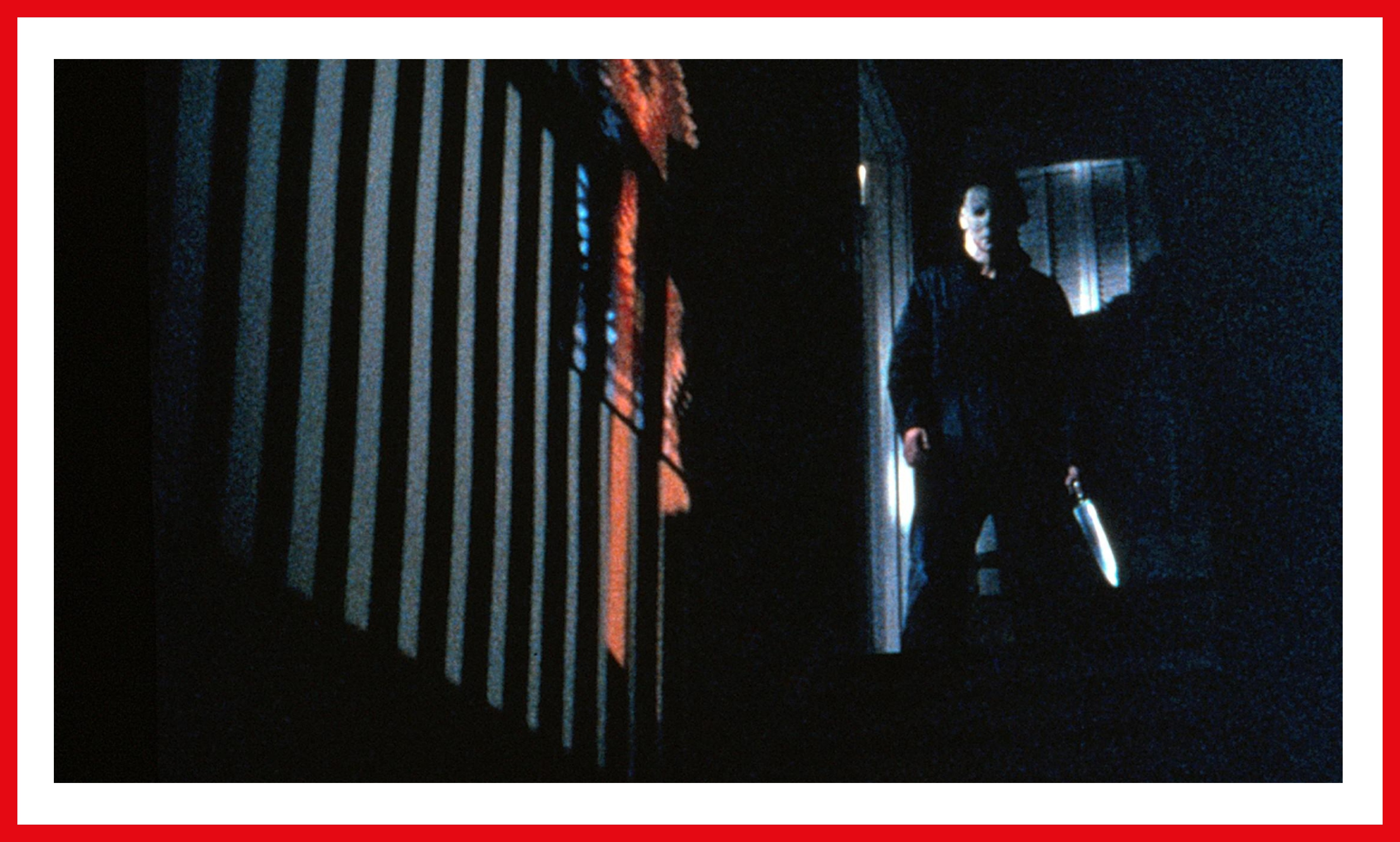 Castle as Michael Myers stands threatening in the dim, the blade of his knife shining.