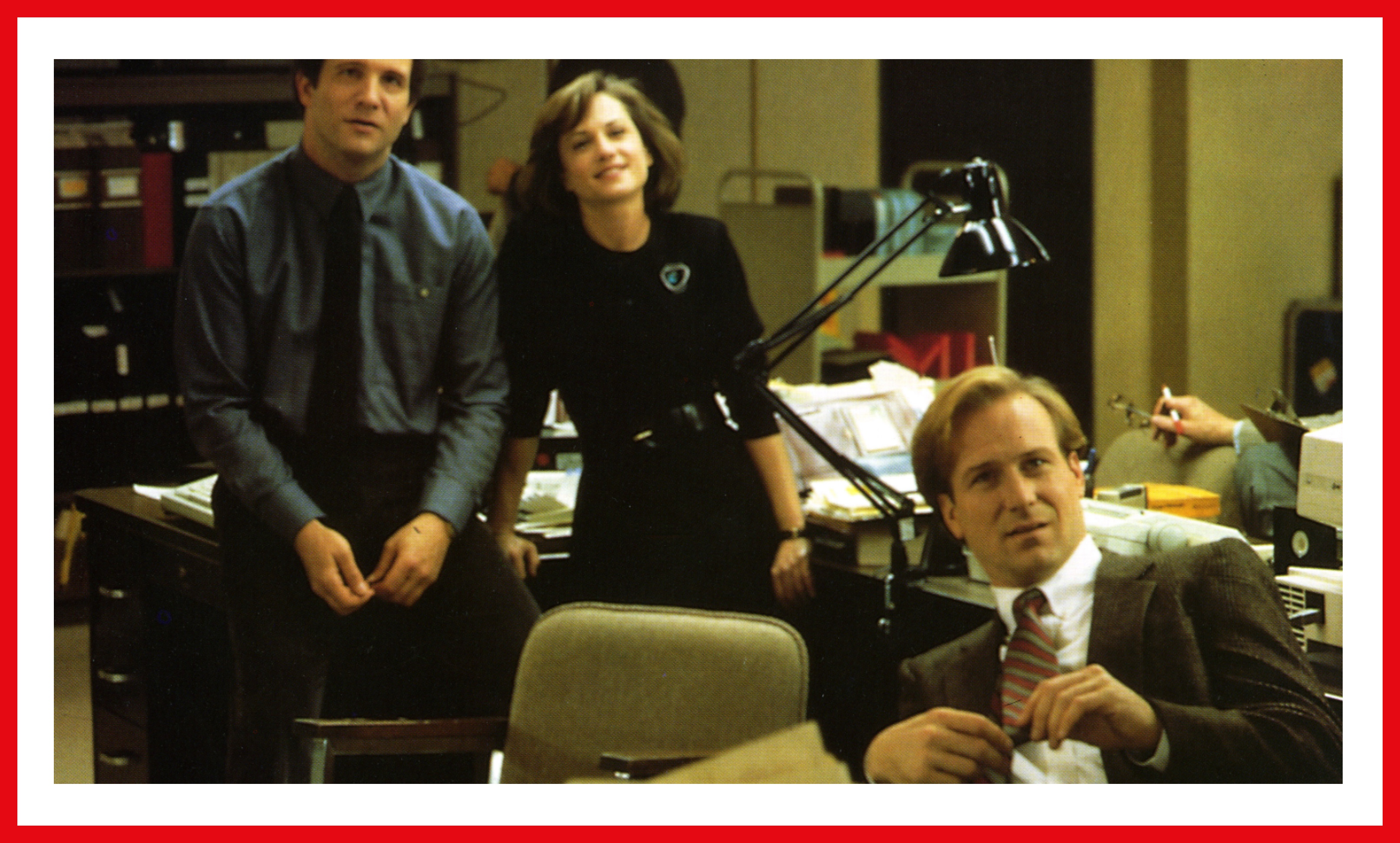 Brooks, Hunter, and Hurt in a scene from the film. They are pictured in a messy newsroom office.