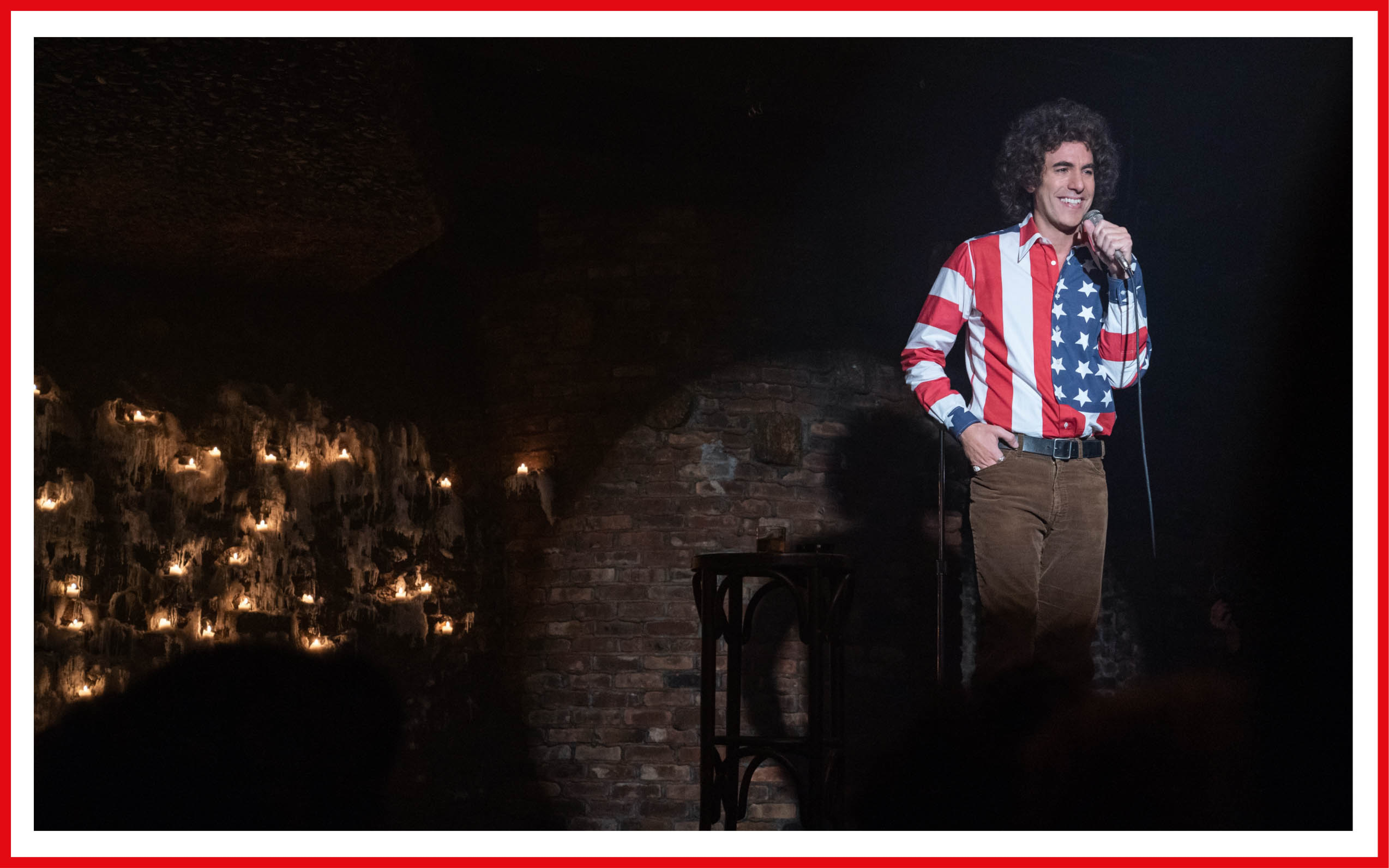 Sacha Baron Cohen, as Abbie Hoffman, stands grinning at a mic, wearing an extremely loud American-flag shirt. The sleeves are stripes, the cuffs are stars.