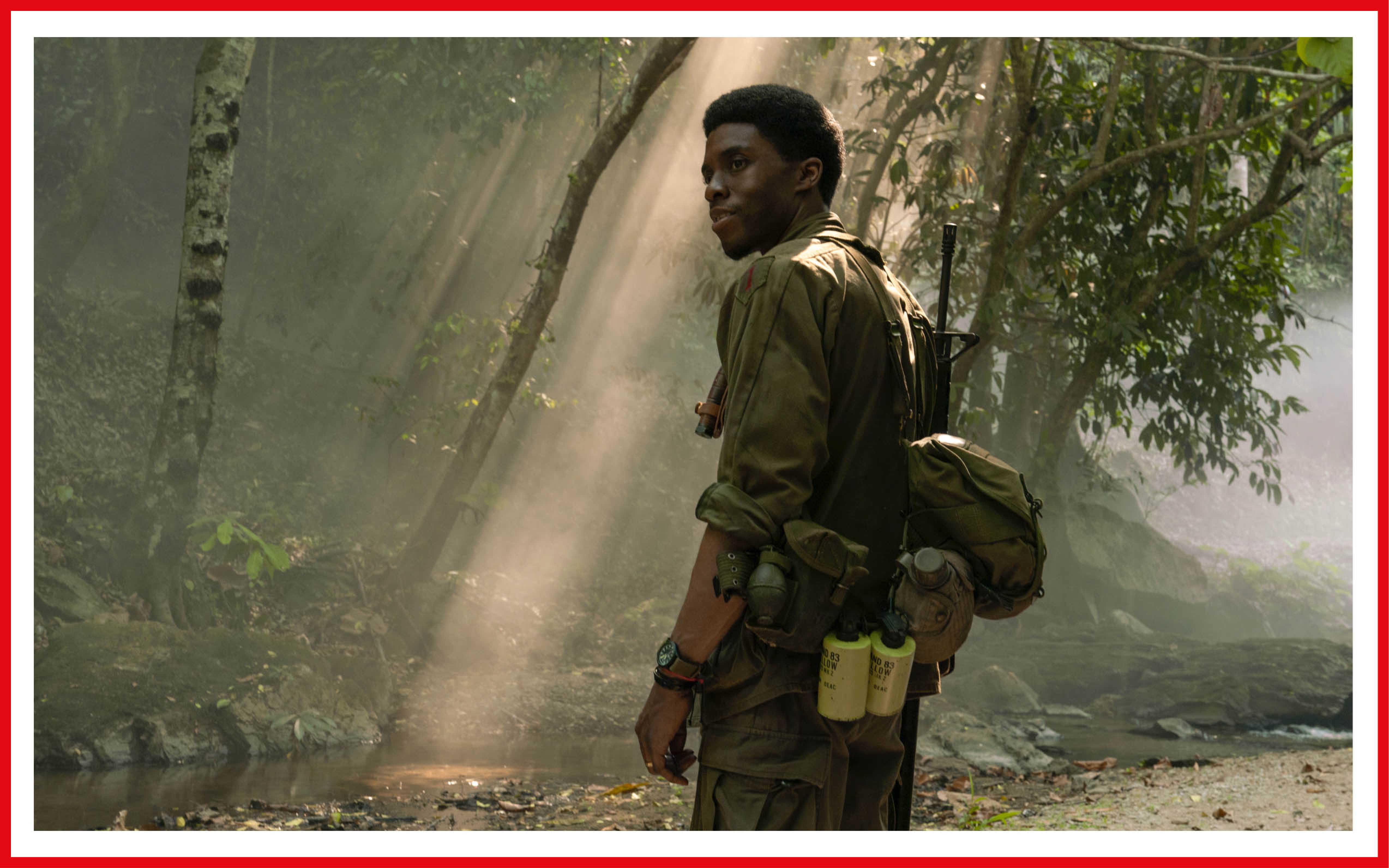 Chadwick Boseman is dressed in military fatigues and standing in dappled jungle light during one of the film's flashback sequences