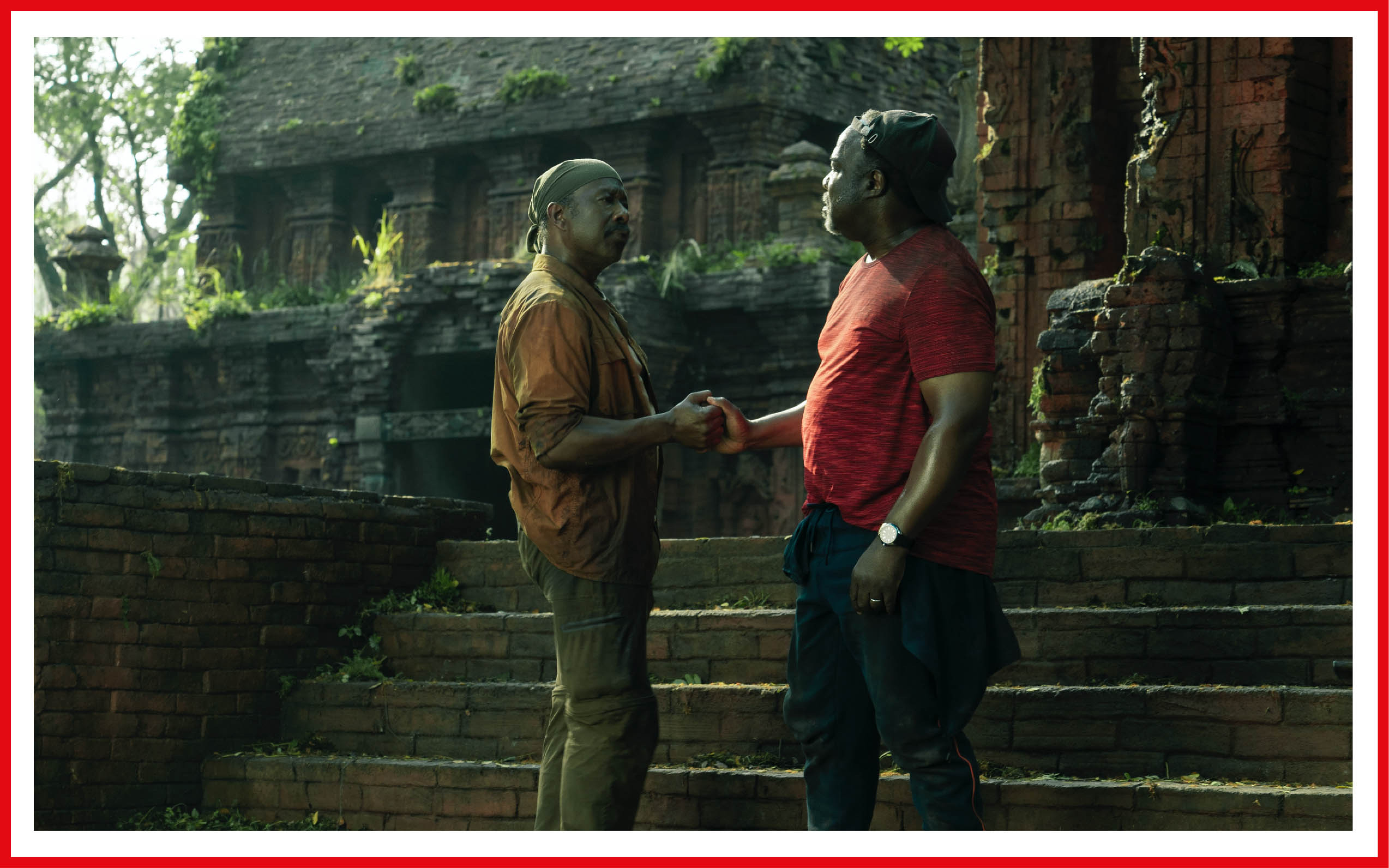 Looking worn from their characters' quest, Clarke Peters and Isiah Whitlock Jr. dap in front of stone ruins