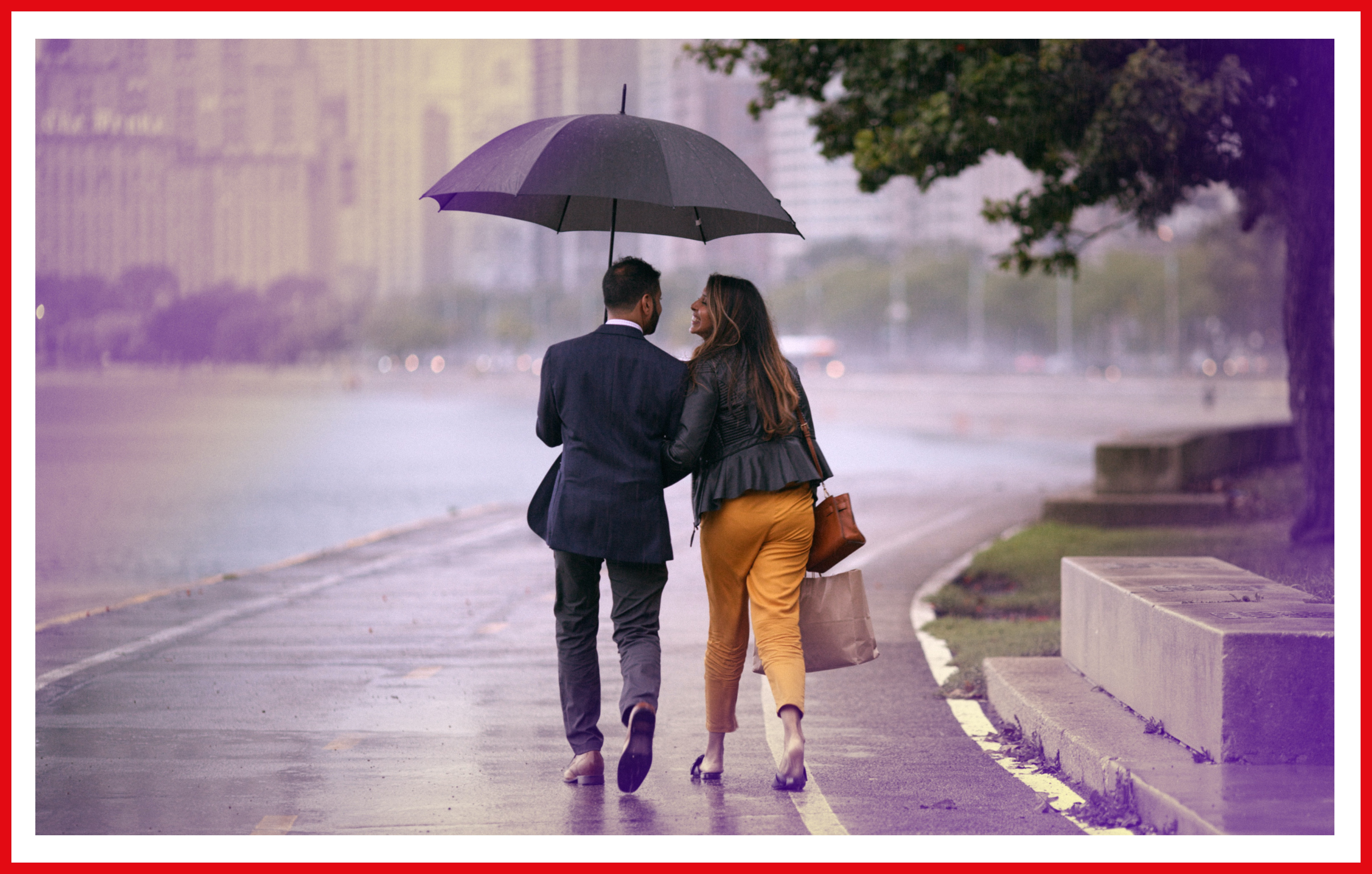 The couple walk down a rainy street.