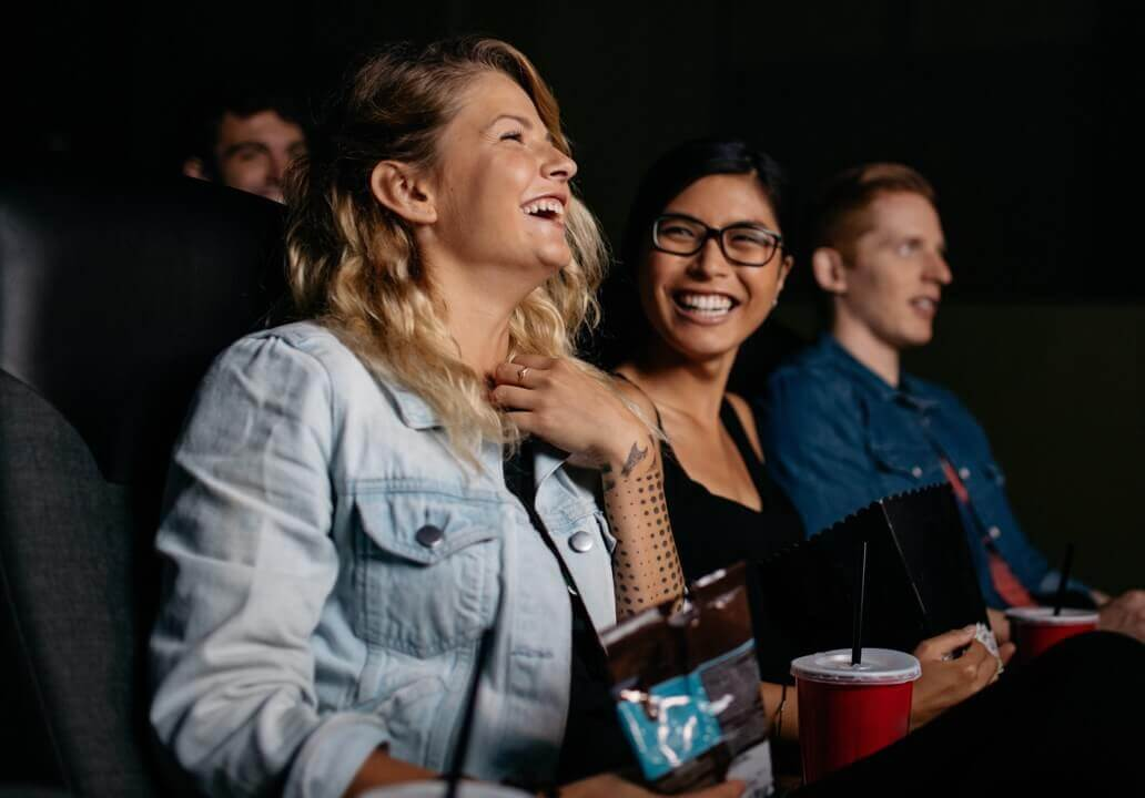 A group of friends happily watching a film in a cinema together and laughing.