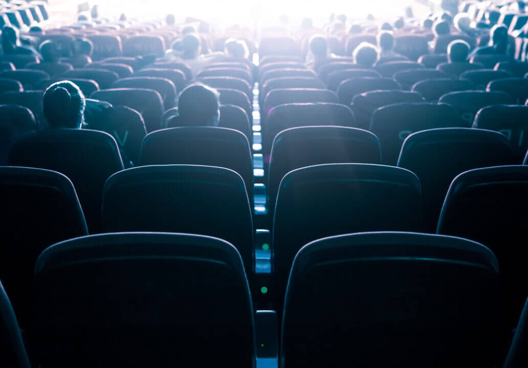 A view from the back of a cinema; looking out over the audience as they bask in the glow of the screen's light.